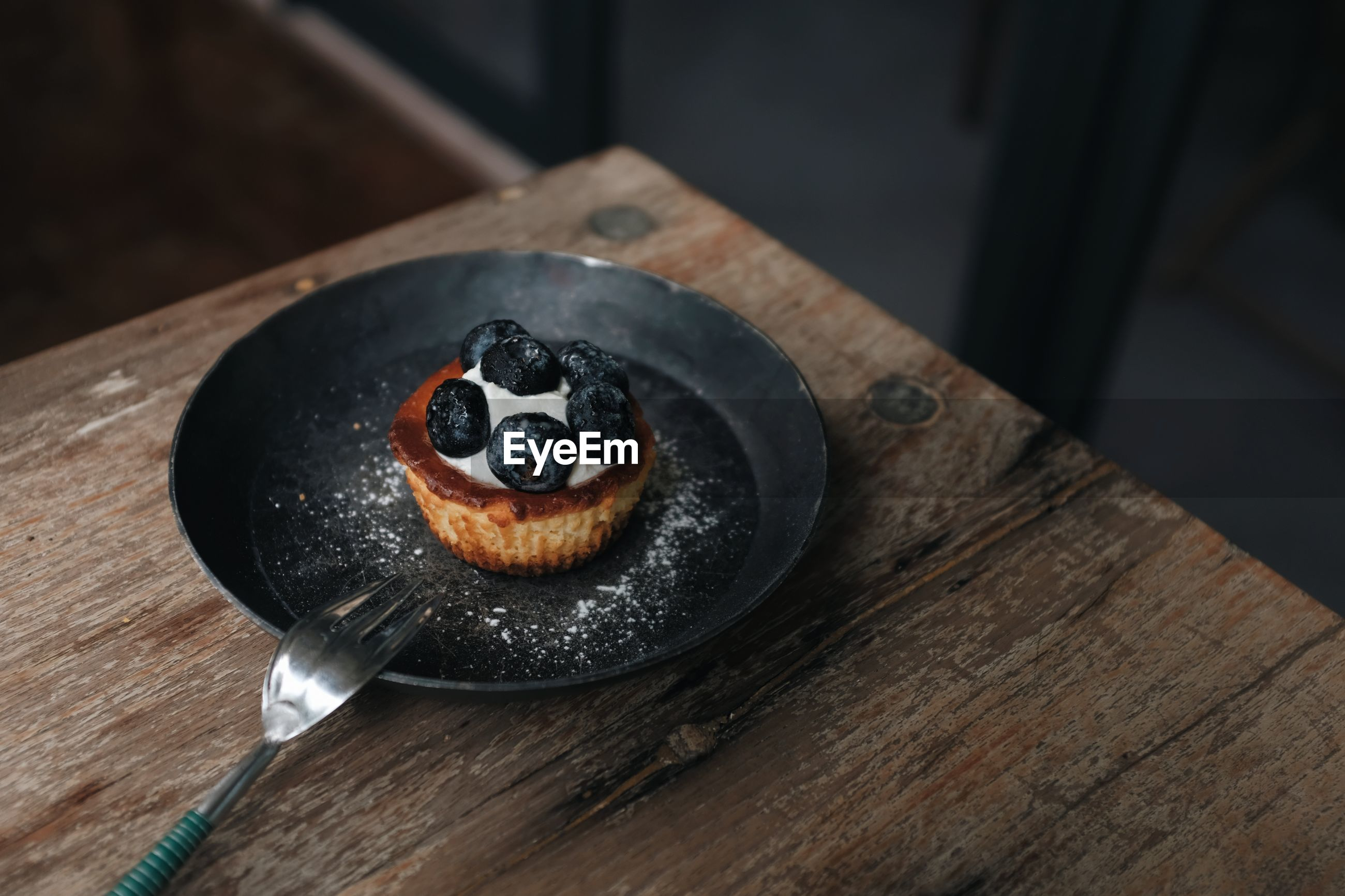 A close up view of a blueberry cheesecake on a black plate placed on a wooden table in a coffee shop