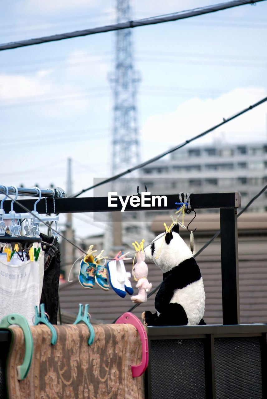 Panda Toy On Roof With Shoes And Clothes Hanging