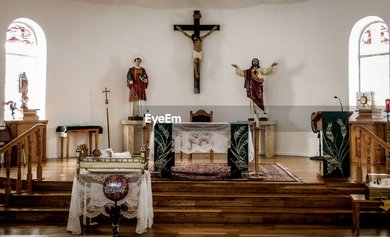 religion, place of worship, belief, spirituality, indoors, cross, art and craft, altar, human representation, sculpture, architecture, male likeness, no people, representation, statue, crucifix, antique