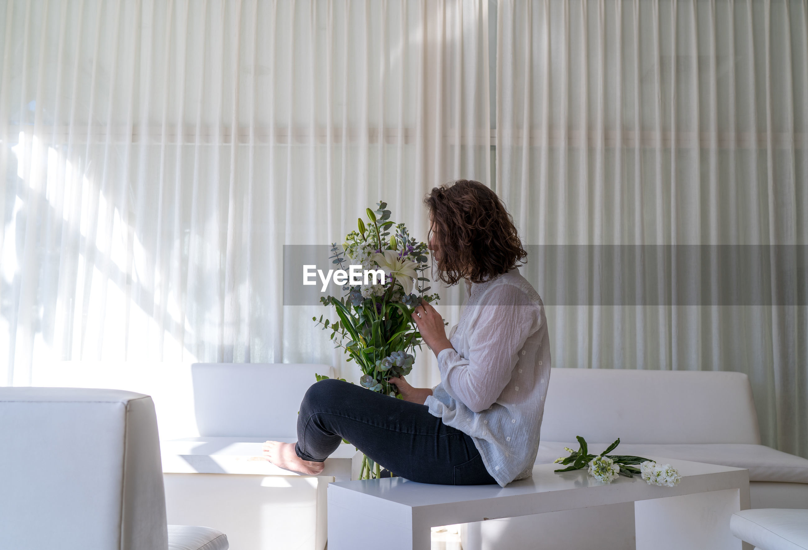Woman sitting on table by potted plant