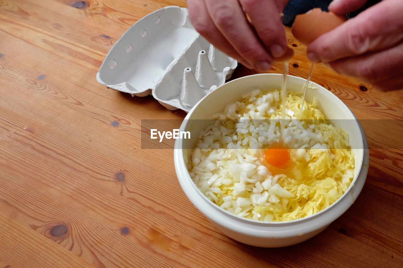 Cropped hands of man breaking egg yolk in bowl on table