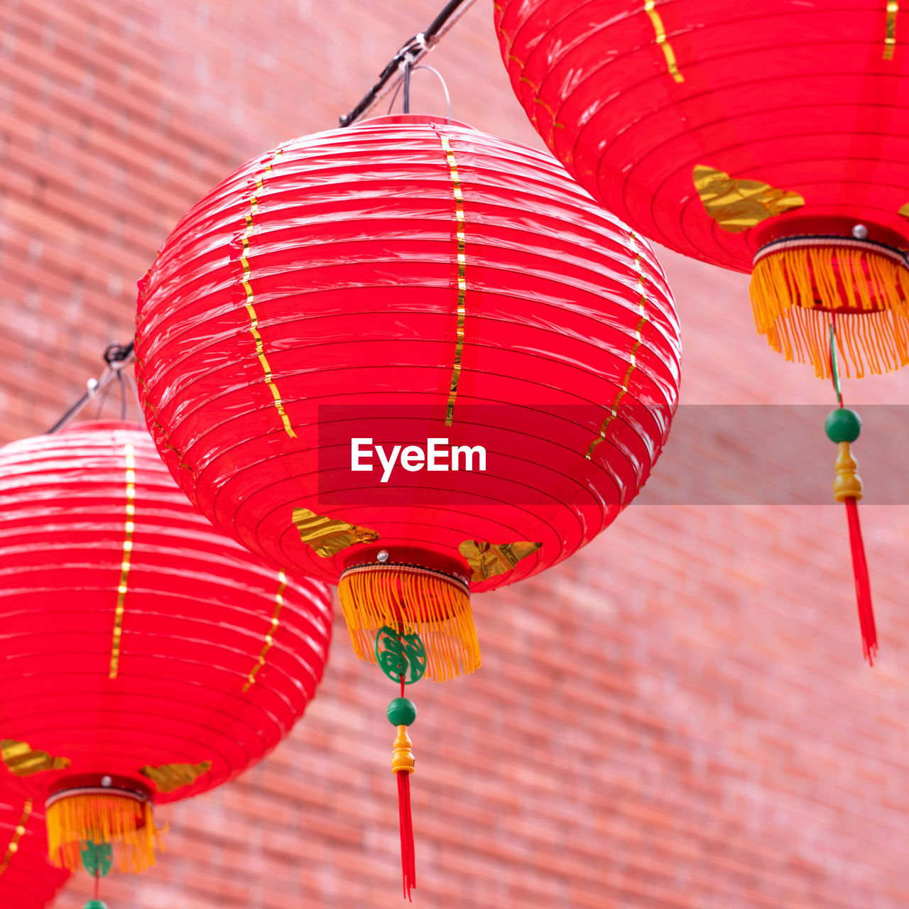 LOW ANGLE VIEW OF LANTERNS HANGING IN ROW AGAINST THE BACKGROUND