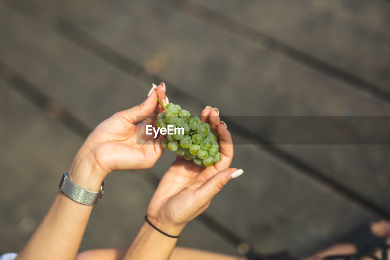 Cropped Hands Of Woman Having Grapes On Boardwalk