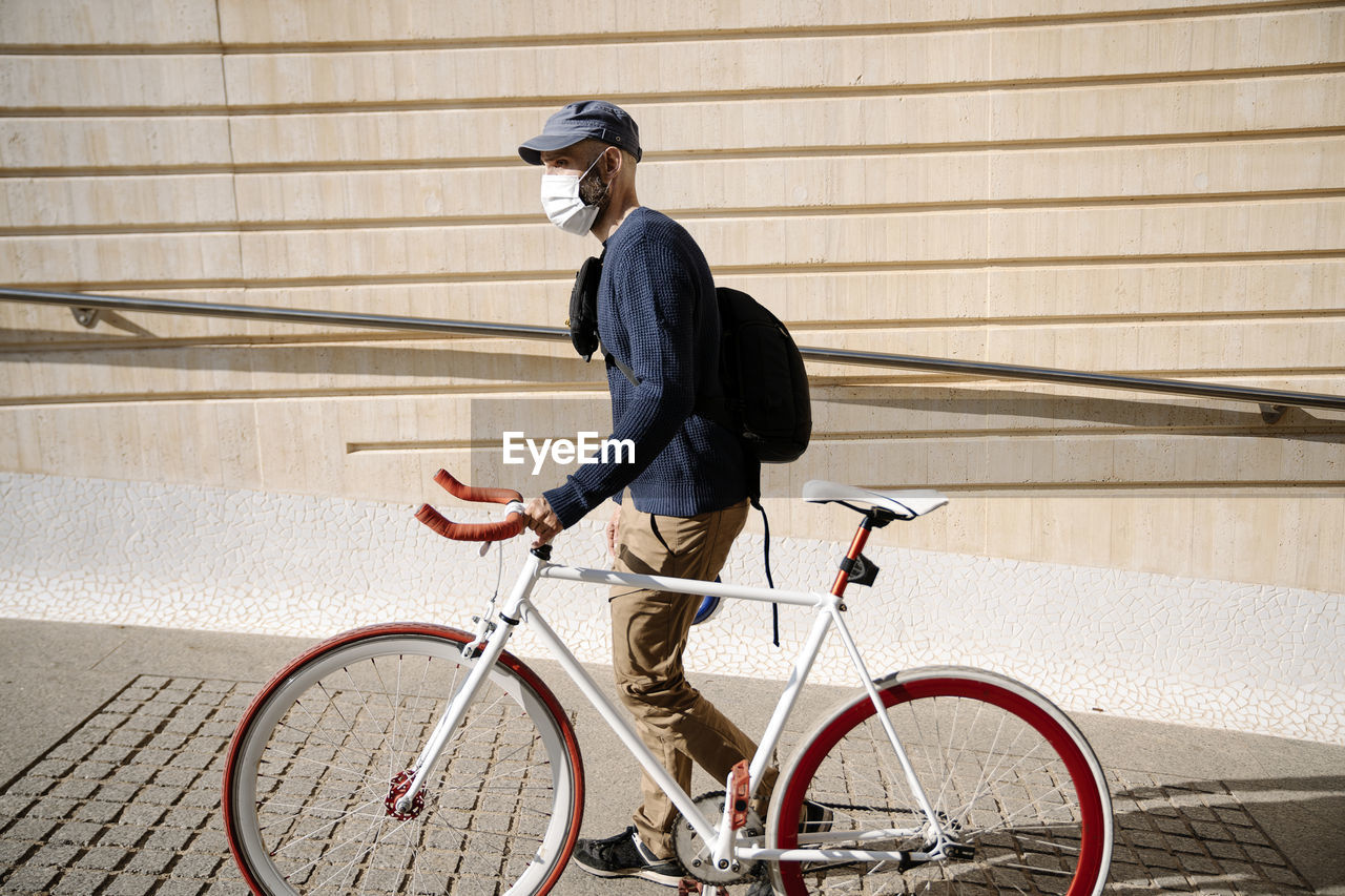 SIDE VIEW OF MAN BICYCLING ON BICYCLE AGAINST WALL