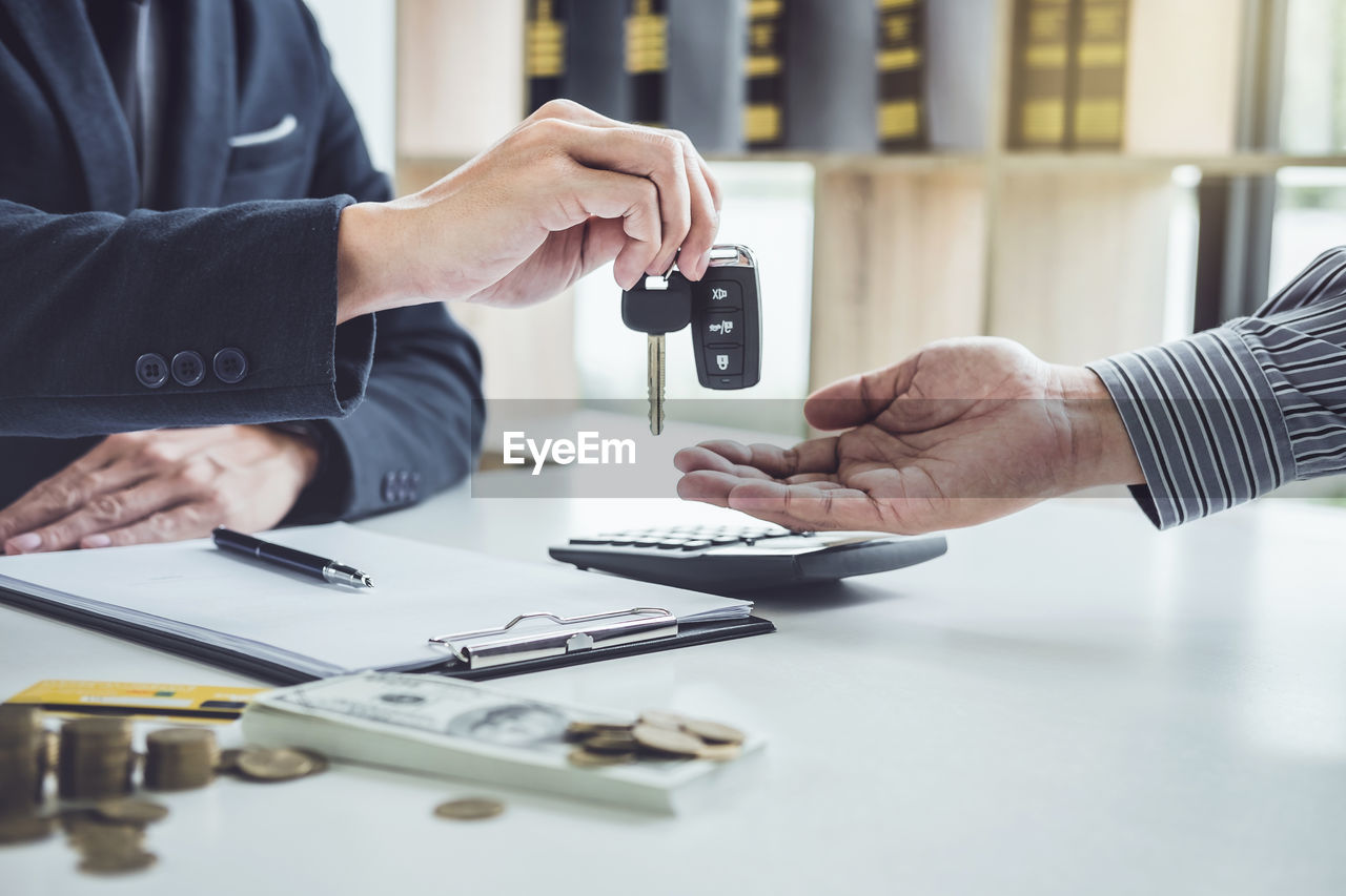 Midsection Of Salesman Giving Car Keys To Owner At Desk In Office