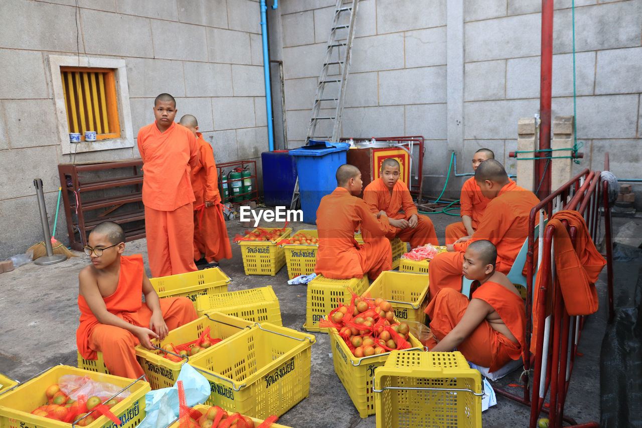 group of people, food, food and drink, men, retail, fruit, healthy eating, sitting, market, people, adult, three quarter length, business, architecture, orange color, day, occupation, women, choice, working, buying