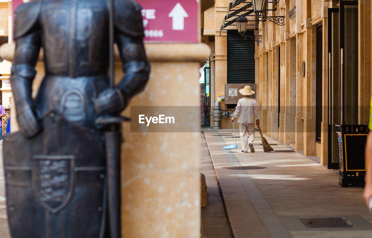 Rear view of male sweeper walking on sidewalk in city