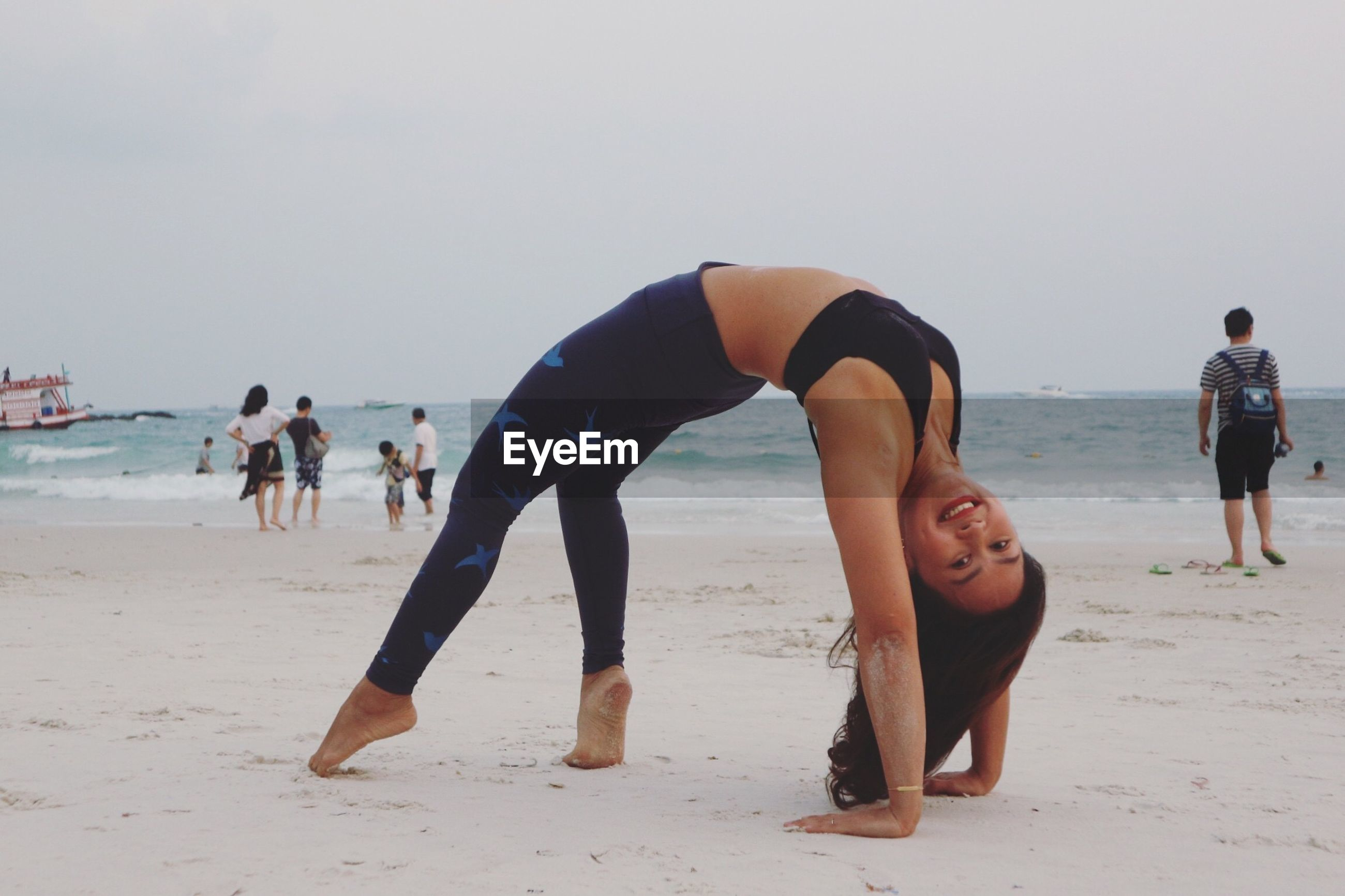 Portrait of smiling mid adult woman bending over backwards at beach