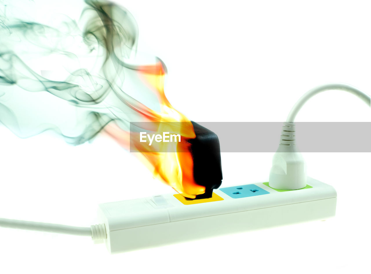 The fire is burning adapter charger plug receptacle on white background, electric short circuit