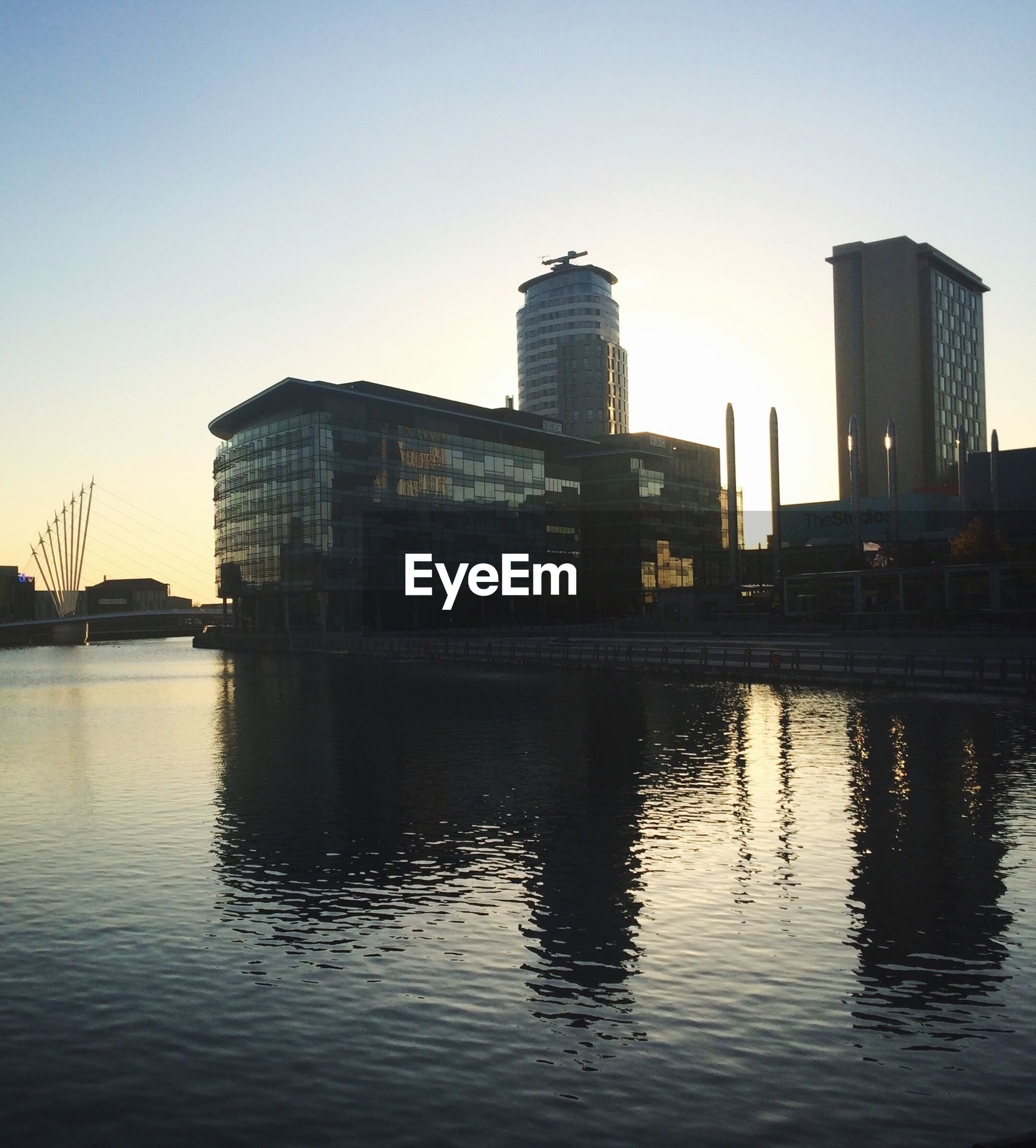 River by modern buildings against clear sky at sunset