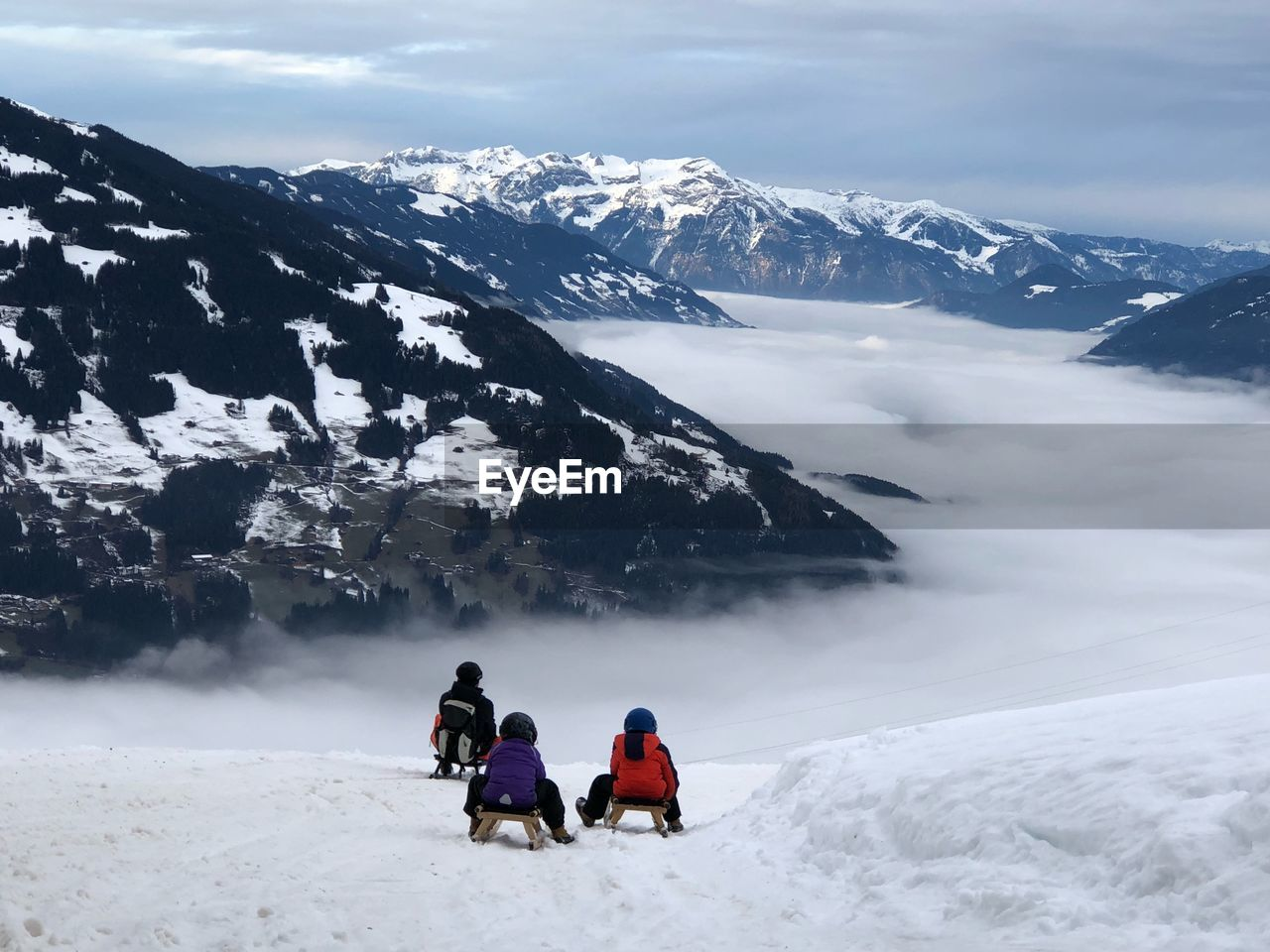 Rear view of friends on tobogganing on snowcapped mountain