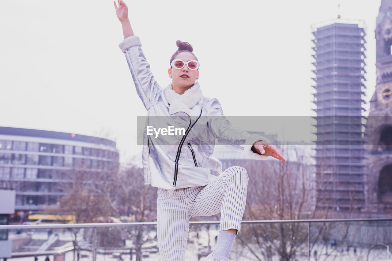 one person, building exterior, architecture, built structure, young adult, real people, leisure activity, young women, lifestyles, standing, clothing, human arm, casual clothing, arms raised, front view, focus on foreground, day, three quarter length, warm clothing, outdoors, beautiful woman, office building exterior, hairstyle