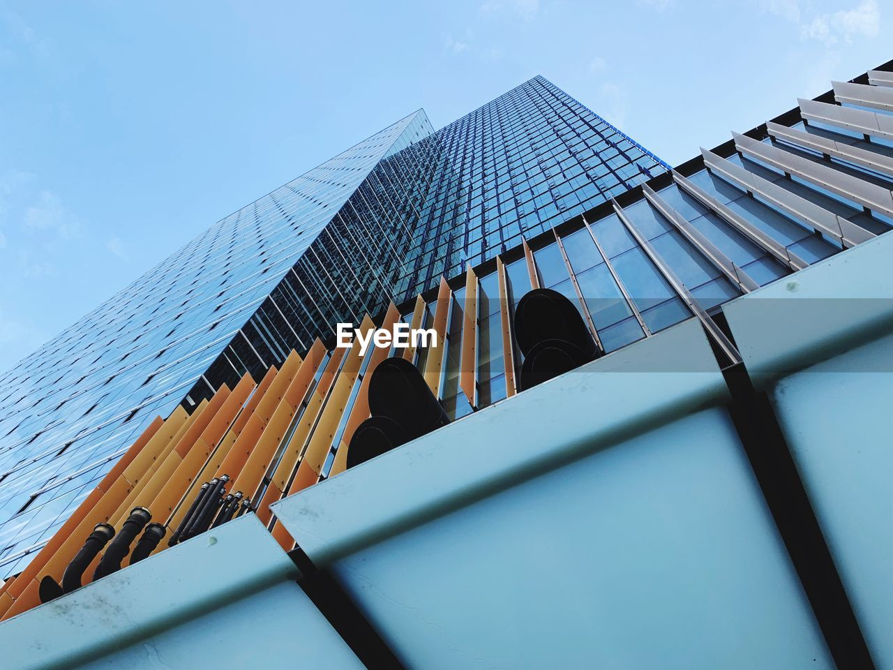 low angle view, built structure, architecture, building exterior, sky, building, office building exterior, day, nature, modern, city, office, skyscraper, tall - high, outdoors, glass - material, reflection, clear sky, real people, men, directly below