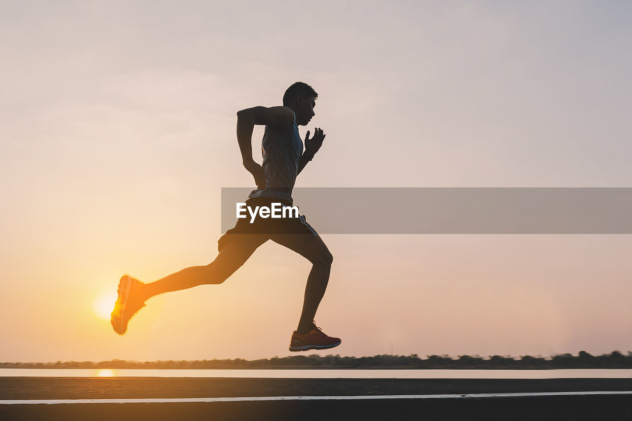 sunset, sky, full length, one person, lifestyles, real people, nature, water, beauty in nature, silhouette, leisure activity, sport, scenics - nature, orange color, mid-air, men, tranquil scene, healthy lifestyle, physical activity, leg