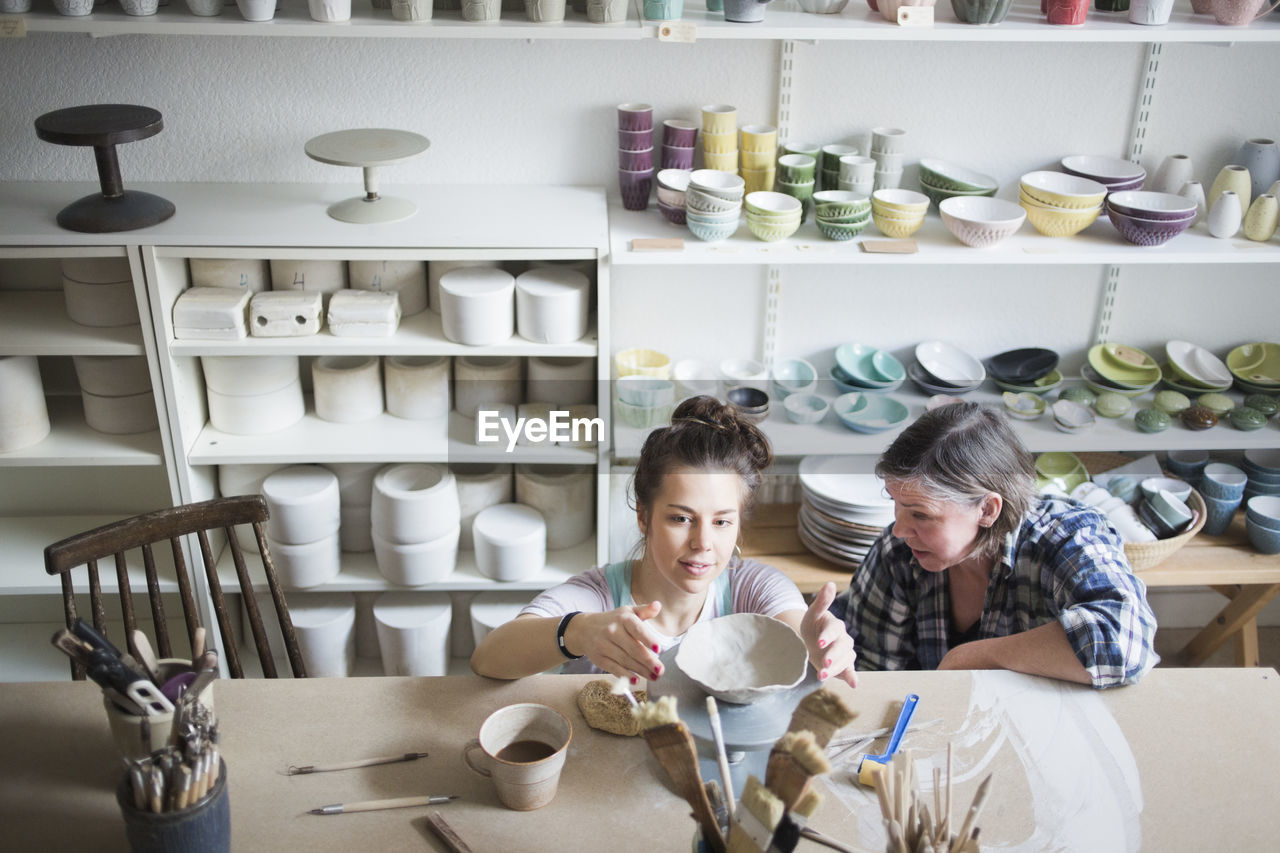 High angle view of mature female potter looking at young craftsperson molding clay at workshop