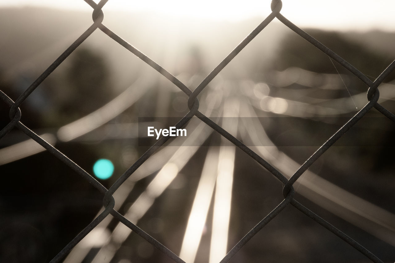 FULL FRAME SHOT OF CHAINLINK FENCE WITH ILLUMINATED WIRE