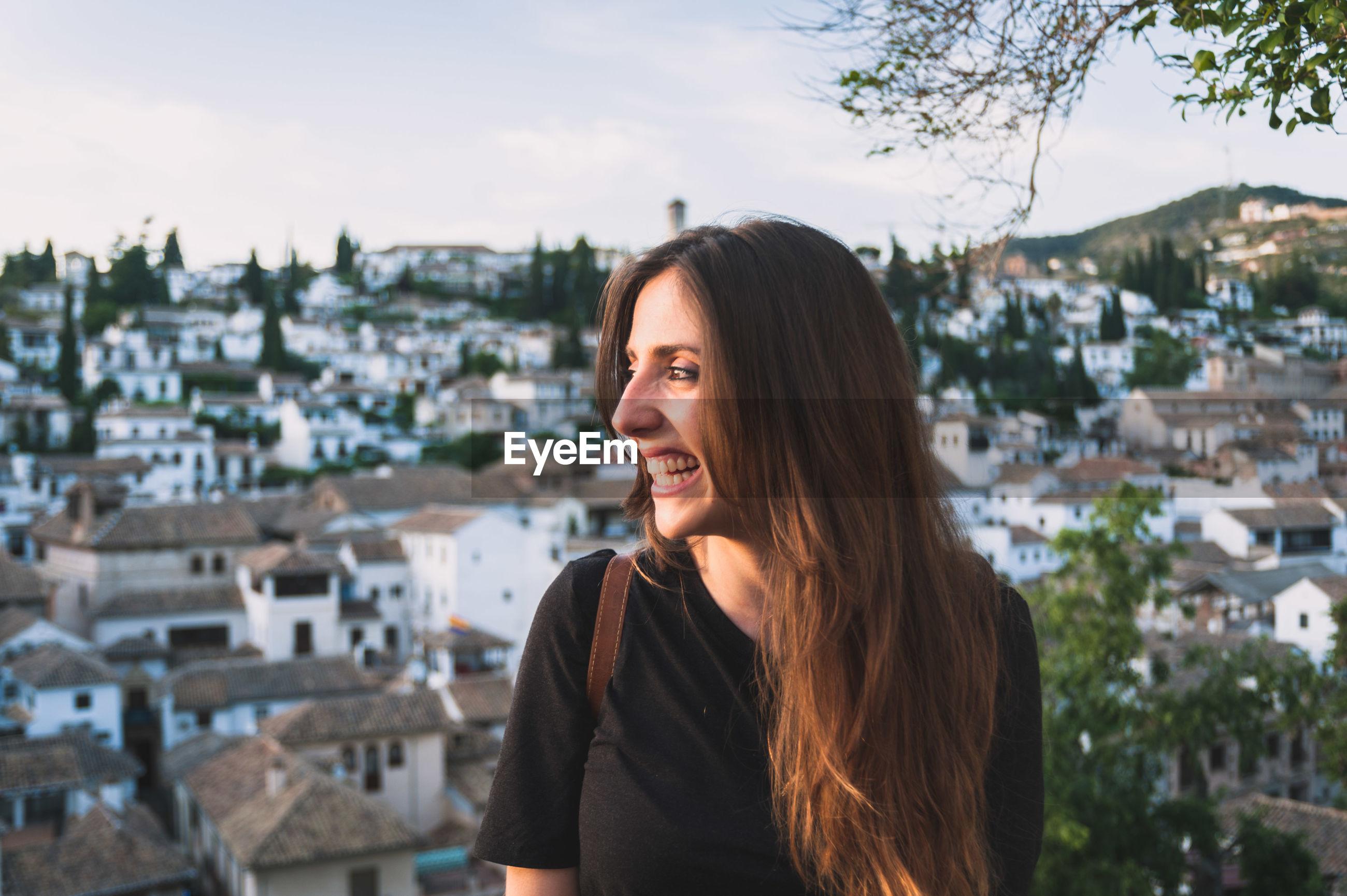 Portrait of young woman against granada cityscape
