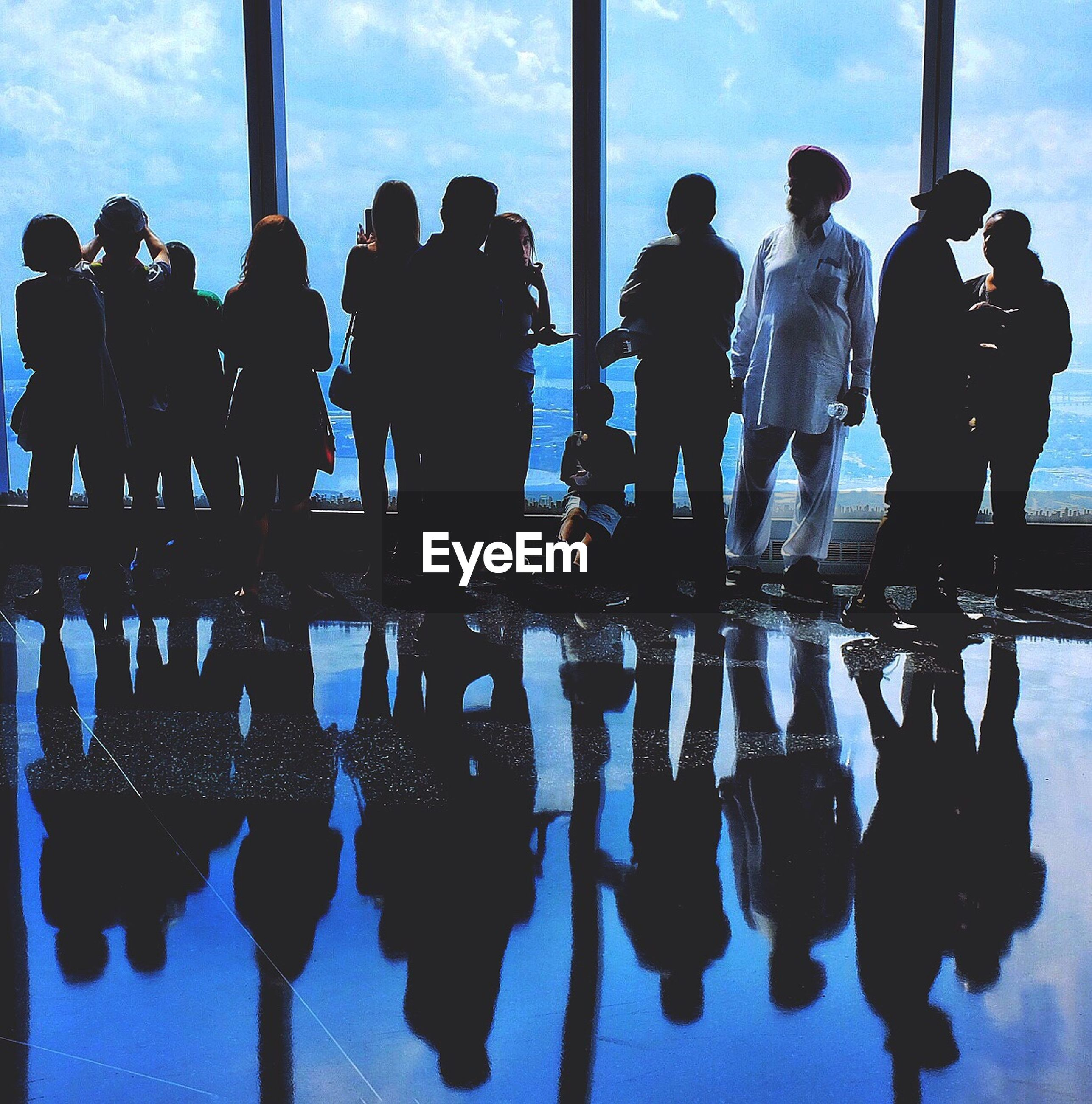 SILHOUETTE OF PEOPLE STANDING BY WINDOW