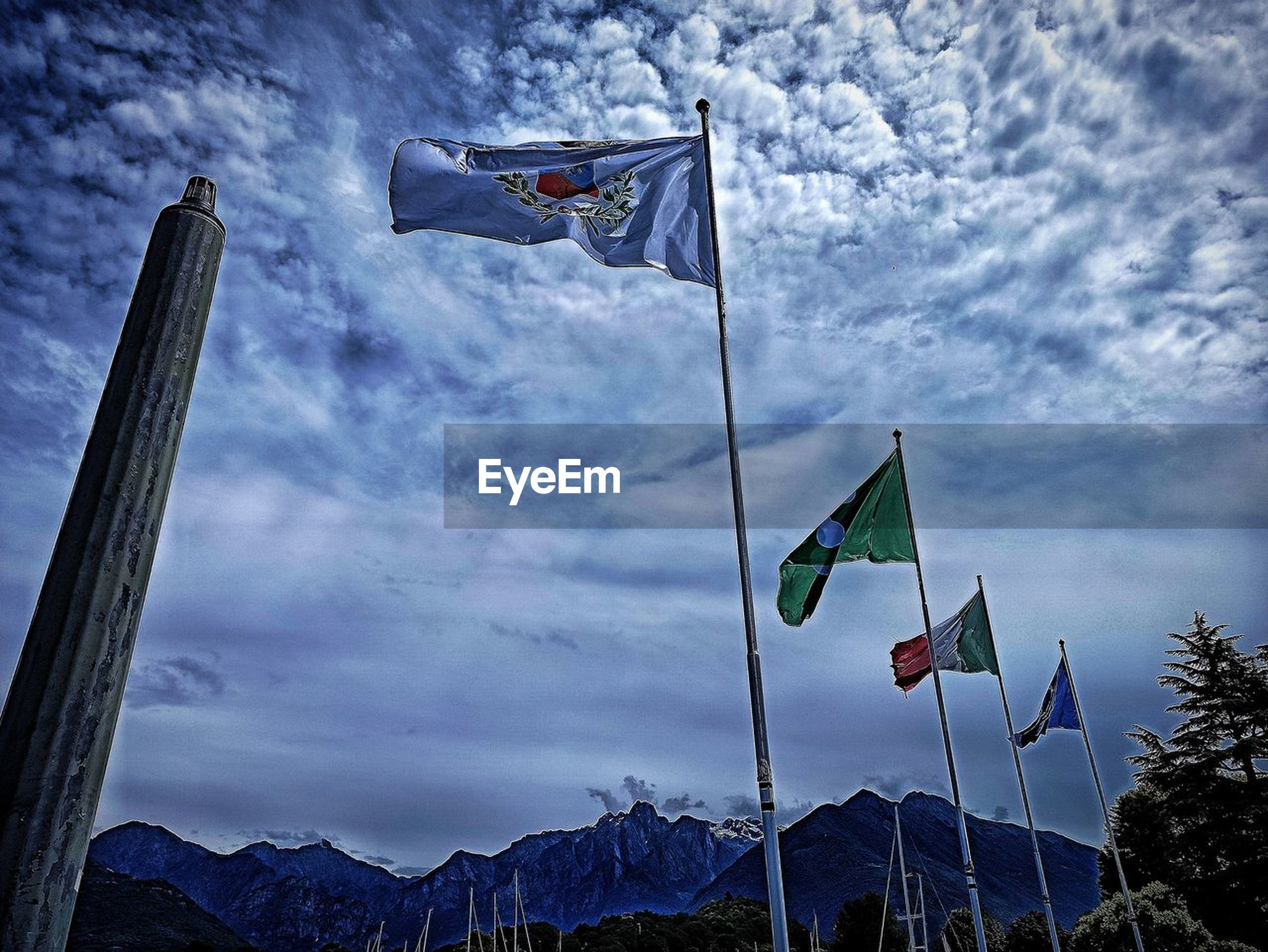 flag, patriotism, sky, environment, nature, cloud, wind, blue, mountain, no people, pole, low angle view, outdoors, mountain range, day