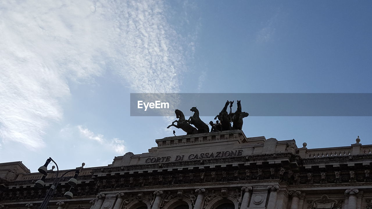 sculpture, statue, architecture, low angle view, built structure, art and craft, building exterior, human representation, sky, outdoors, day, travel destinations, cloud - sky, history, no people, city