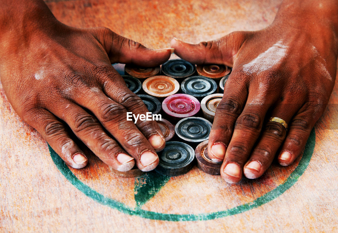 Close-Up Of Hands Around Carom Board Coins