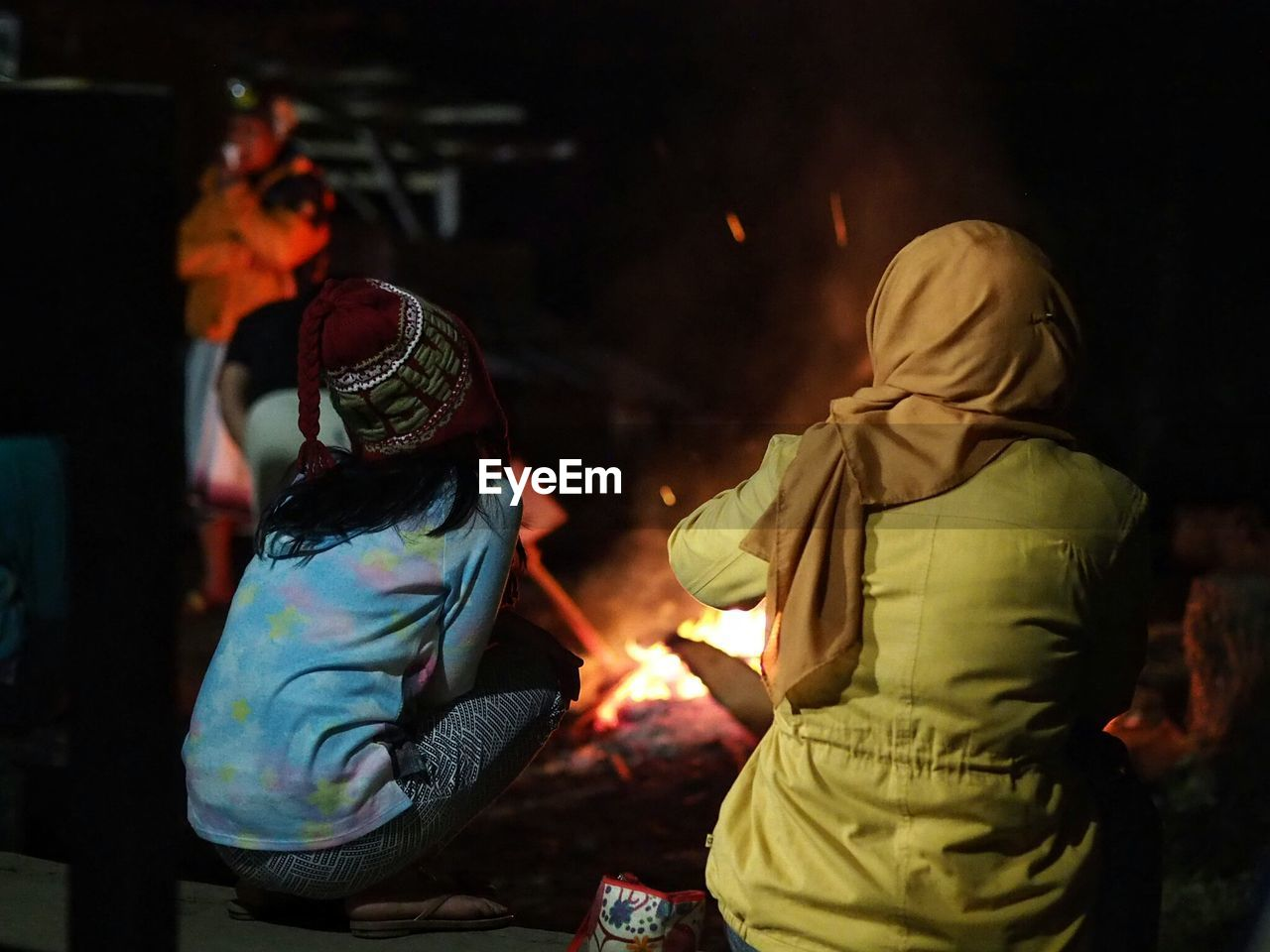 real people, night, burning, traditional clothing, rear view, men, flame, heat - temperature, two people, women, togetherness, lifestyles, illuminated, outdoors, childhood, warm clothing, adult, people