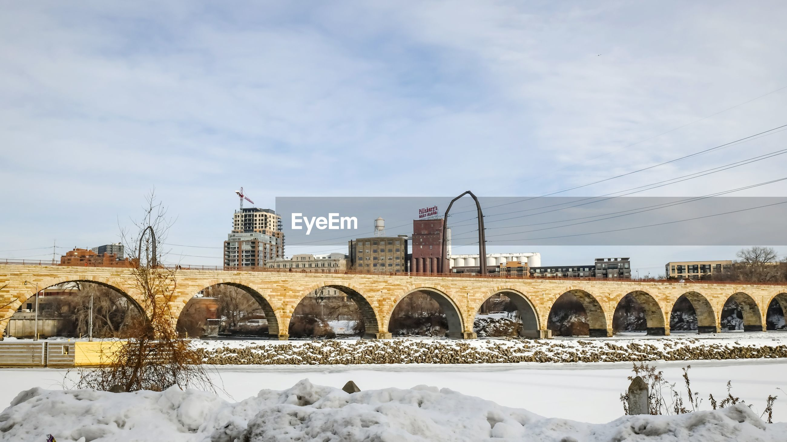 Snow covered arch bridge against sky