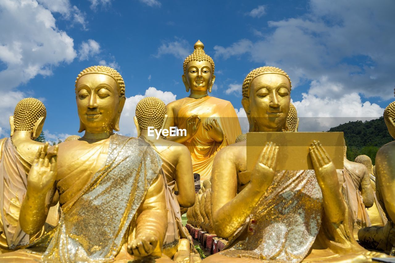human representation, sculpture, male likeness, gold colored, statue, art and craft, representation, belief, spirituality, religion, creativity, no people, sky, idol, gold, low angle view, architecture, large