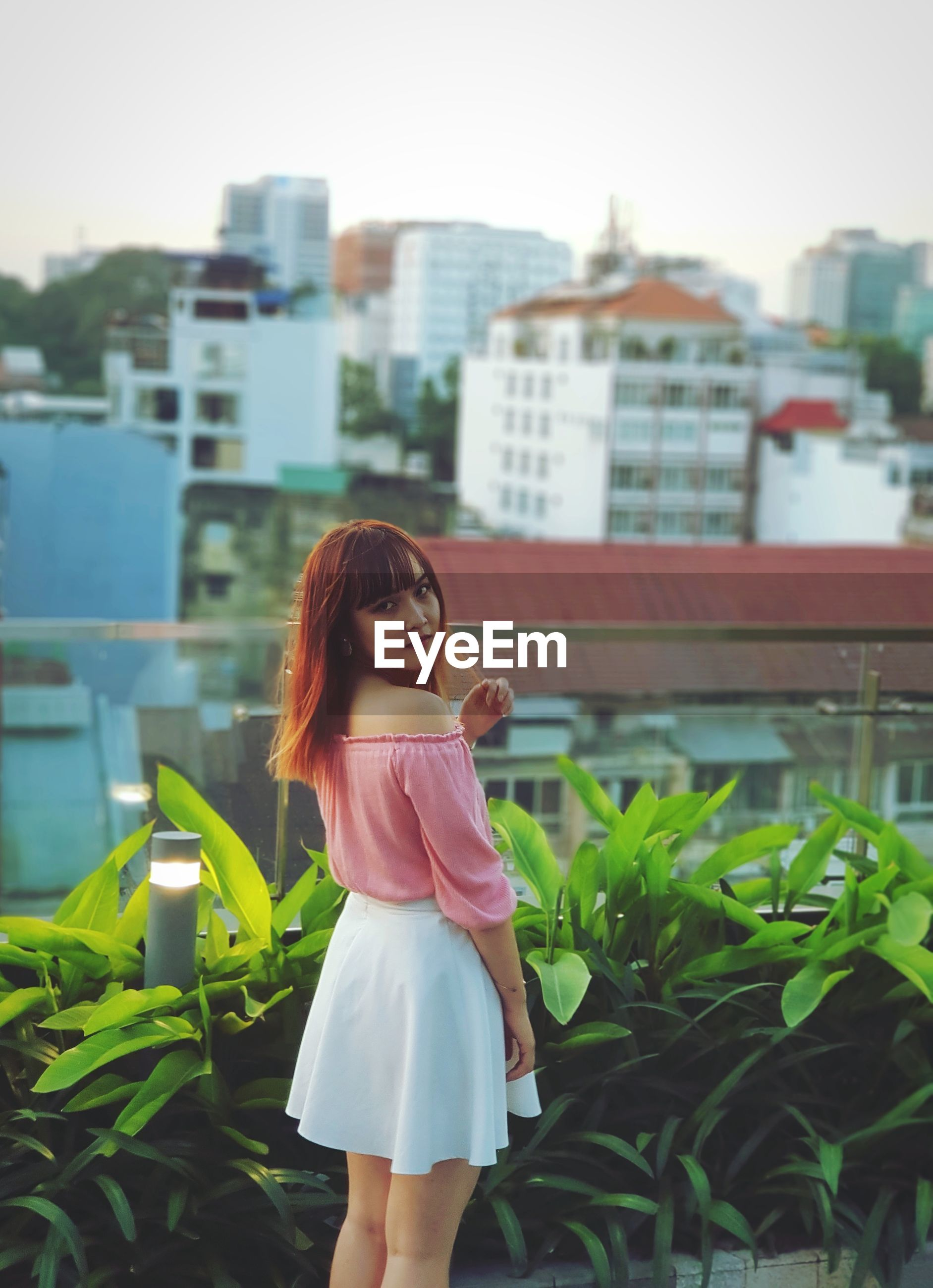 Portrait of young woman standing by plants in city against sky