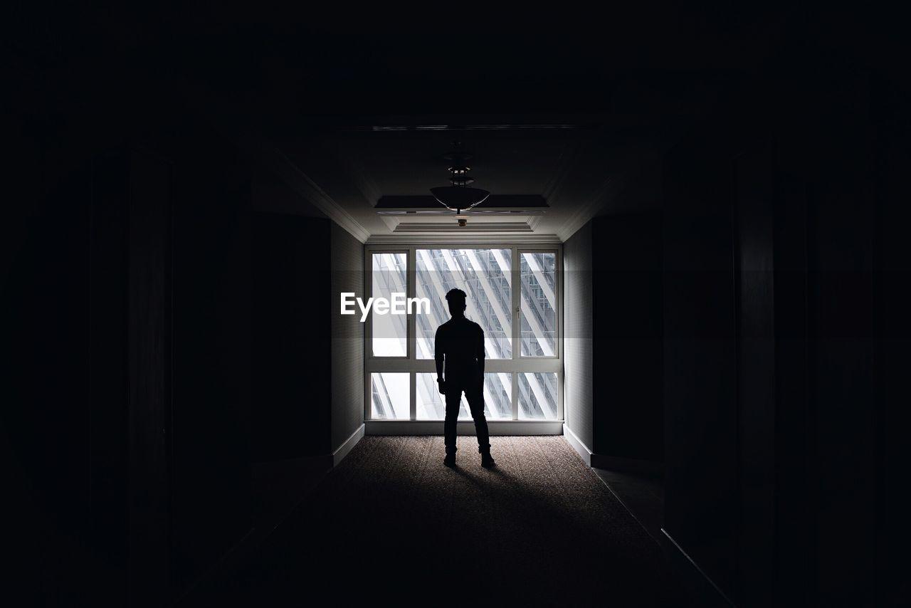 Silhouette man standing in dark corridor against window