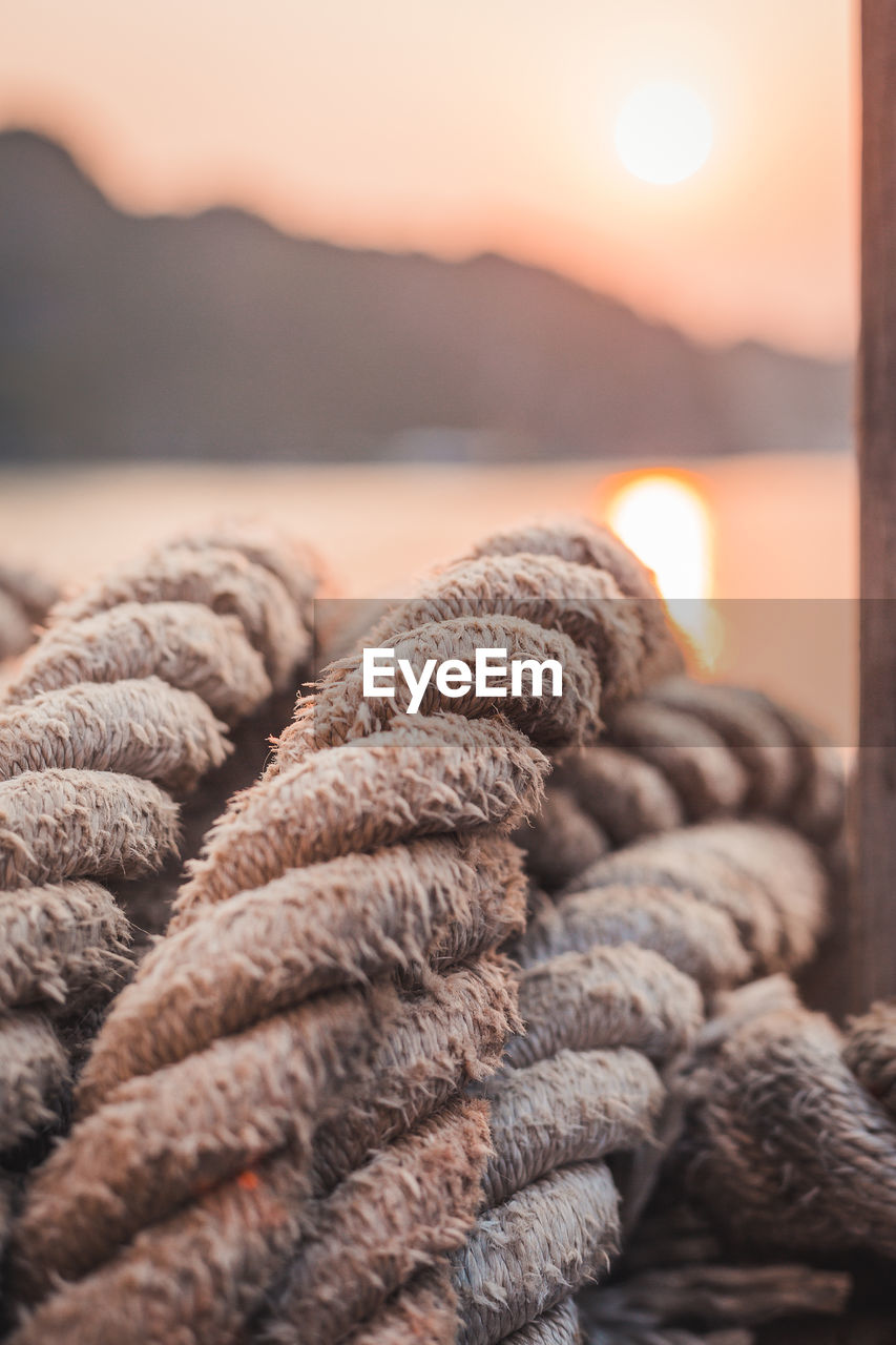 water, sunset, sea, close-up, rope, no people, sky, focus on foreground, strength, nature, outdoors, sun, textured, beauty in nature, beach, selective focus, pattern, large group of objects, stack
