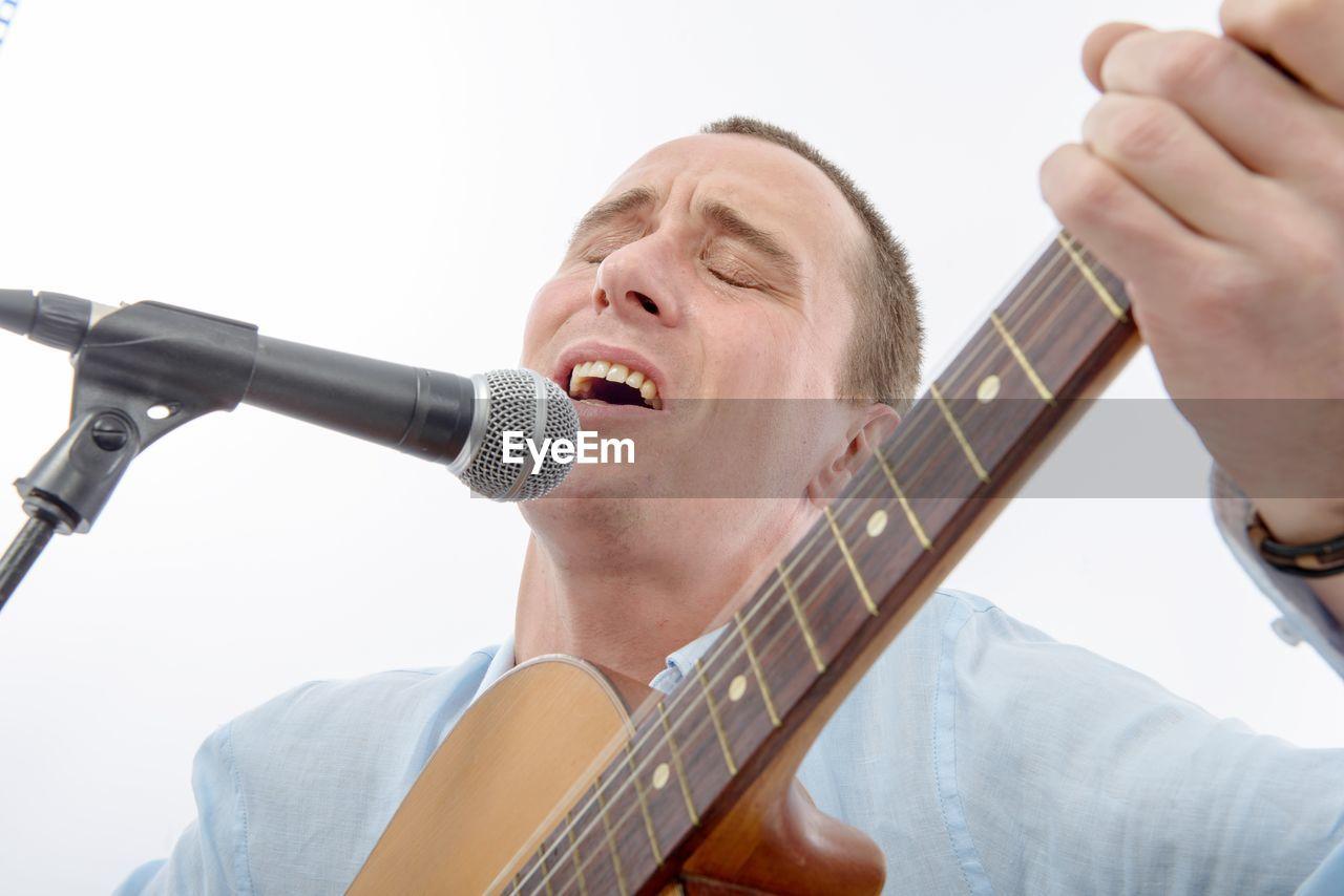 Man singing against white background