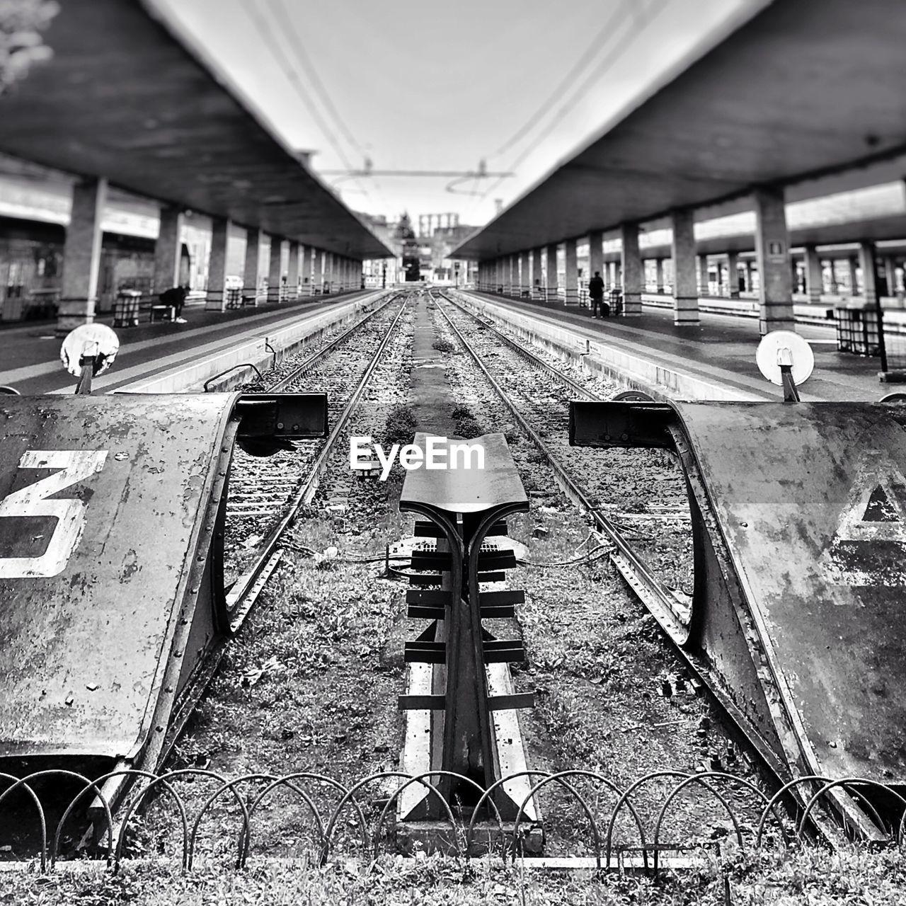 Railroad tracks on station against sky