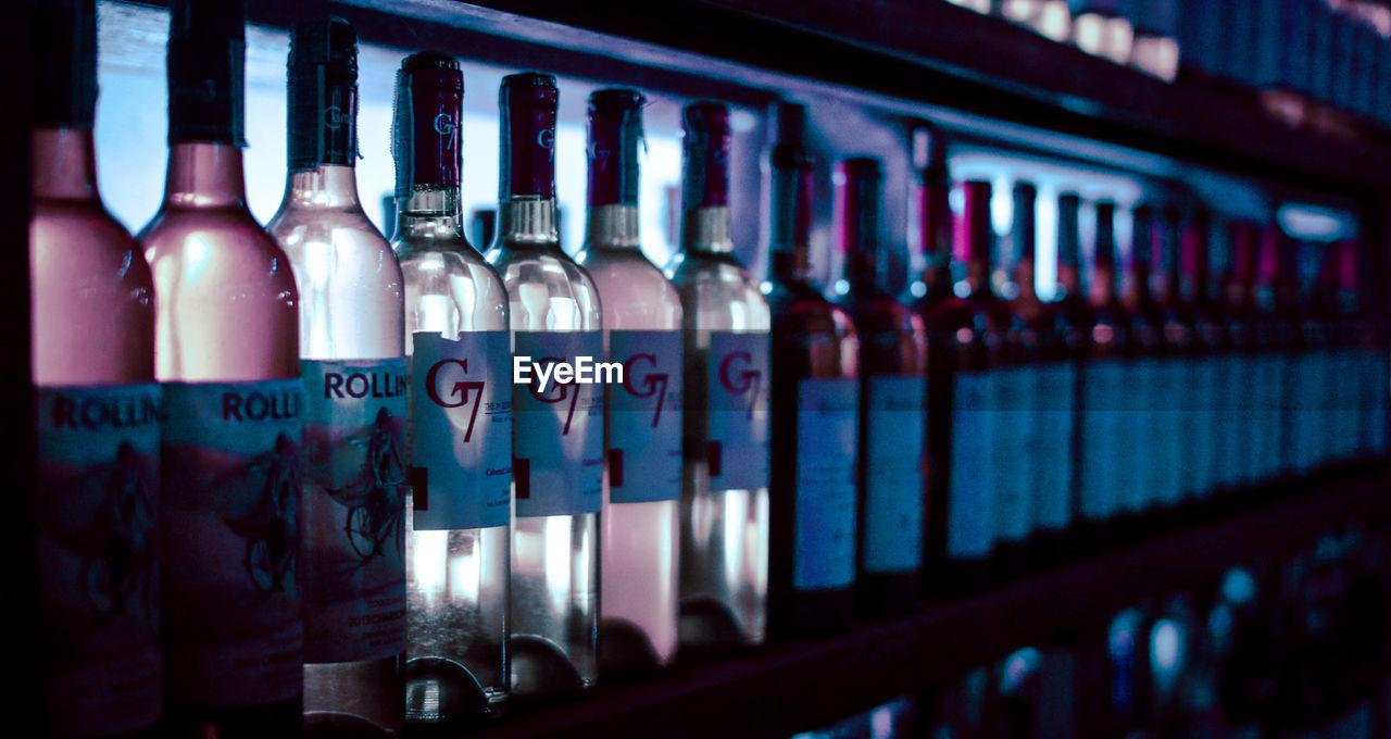 CLOSE-UP OF WINE BOTTLES ON SHELF IN BAR
