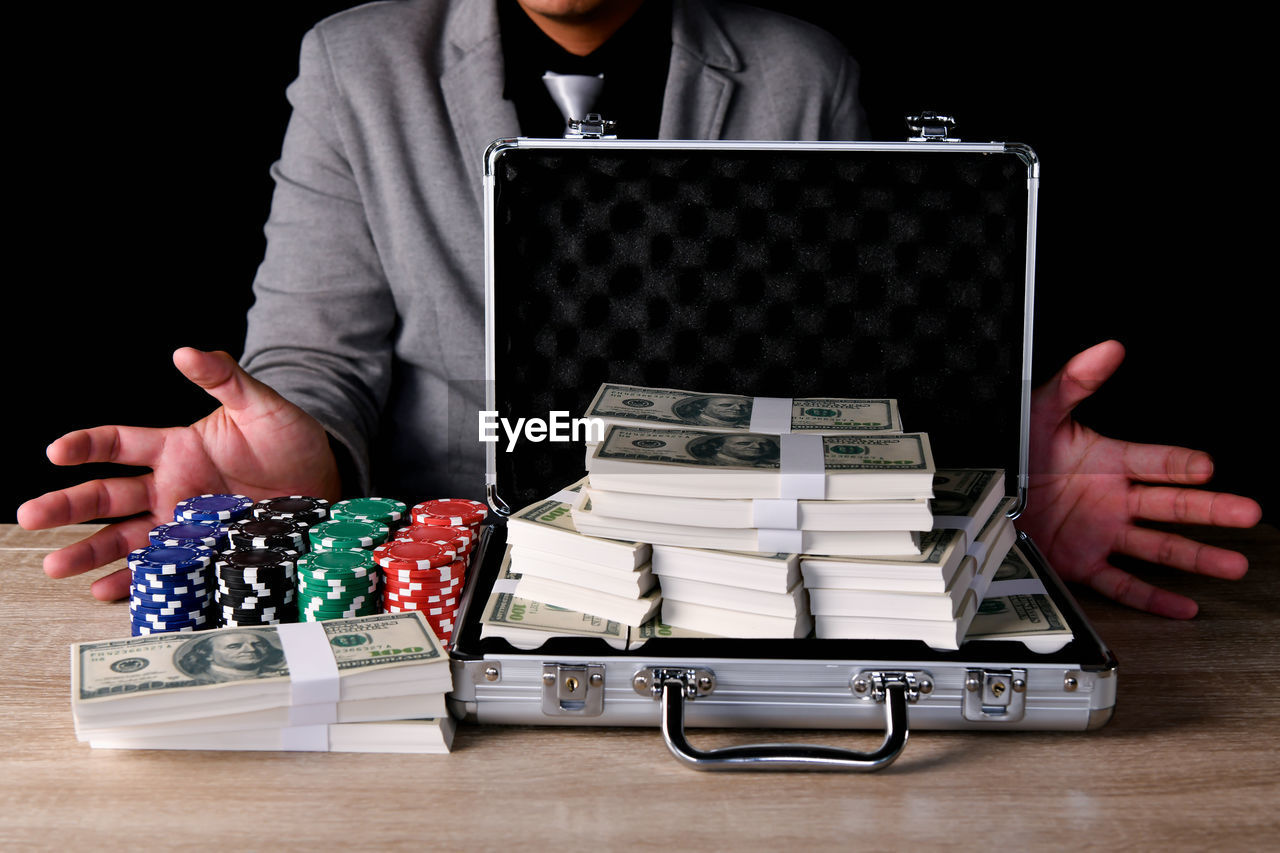 Midsection of man with gambling chips and paper currency in briefcase against black background