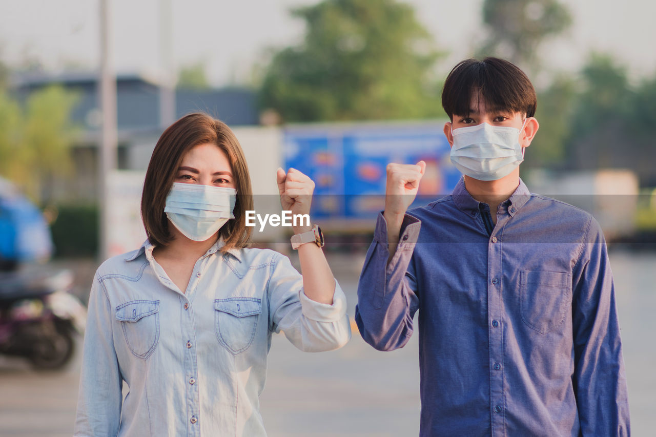 Portrait of couple gesturing while wearing mask standing outdoors