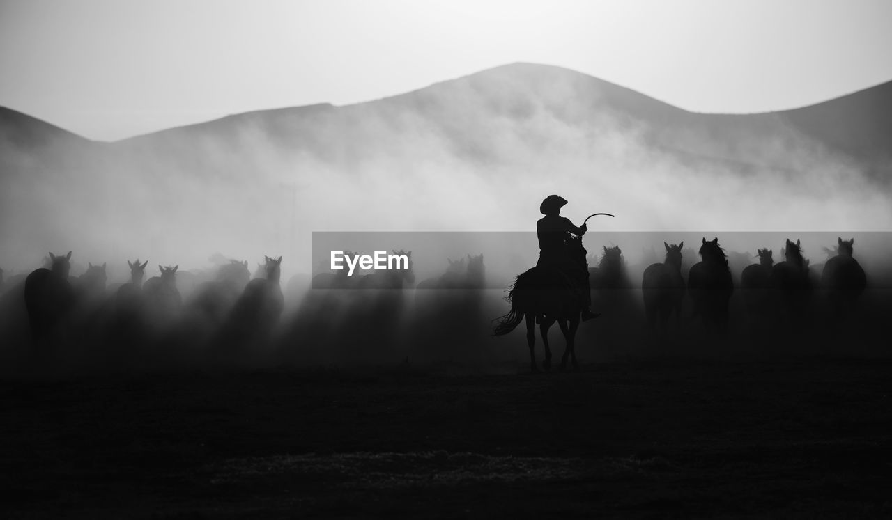 mountain, fog, sky, field, real people, land, nature, silhouette, beauty in nature, landscape, non-urban scene, standing, environment, scenics - nature, people, men, leisure activity, tranquil scene, outdoors