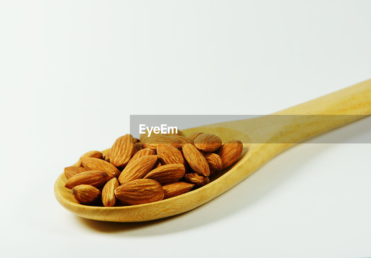 Close-up of almonds in wooden spoon over white background