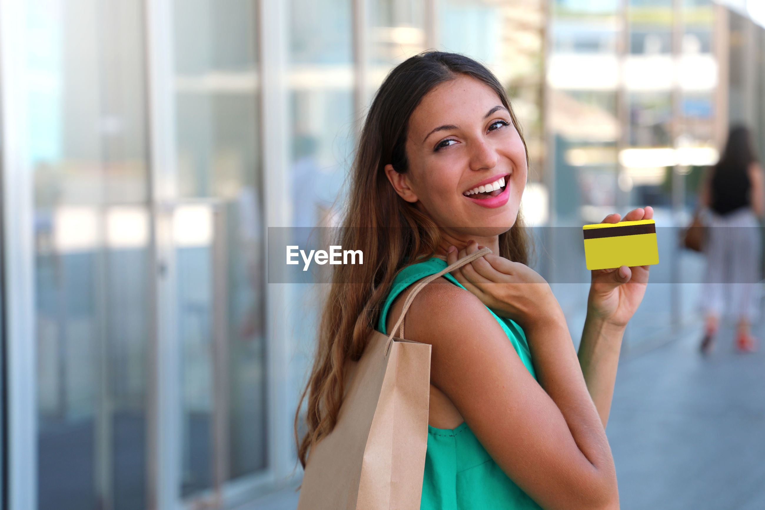 Portrait of cheerful young woman showing credit card while shopping in city