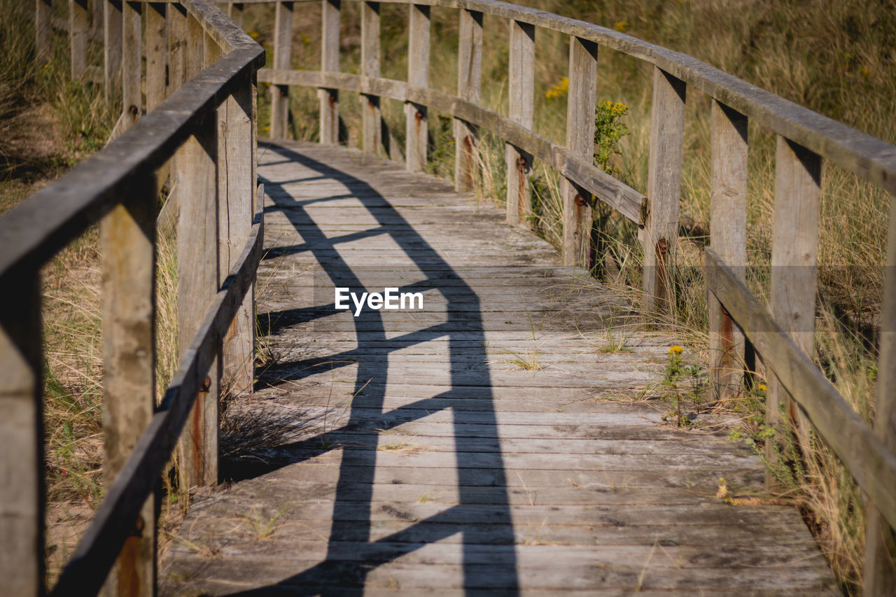 railing, shadow, day, nature, no people, barrier, wood - material, built structure, fence, architecture, sunlight, boundary, footpath, the way forward, direction, security, outdoors, safety, high angle view, protection, wood, footbridge