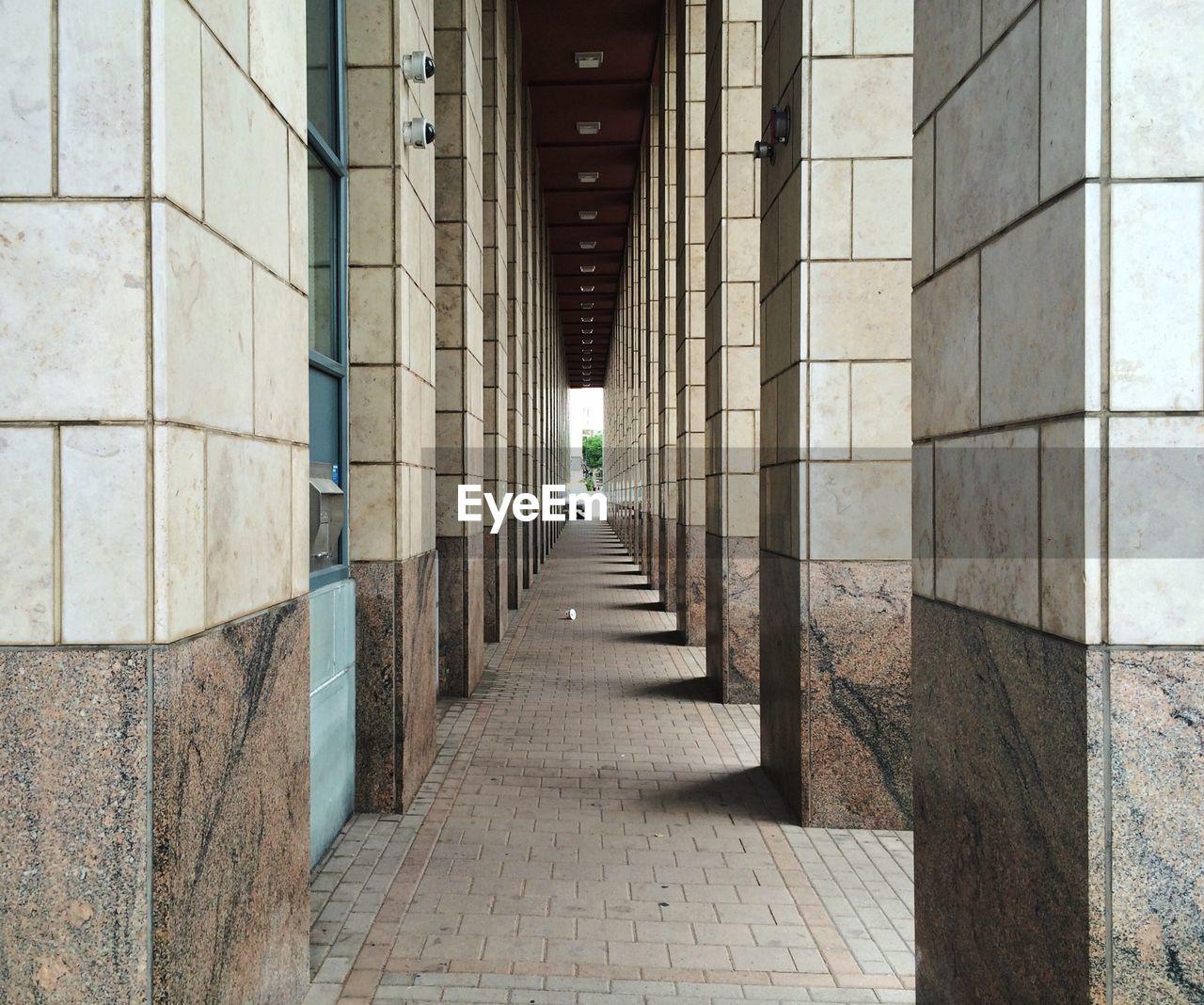 Empty narrow corridor along pillars