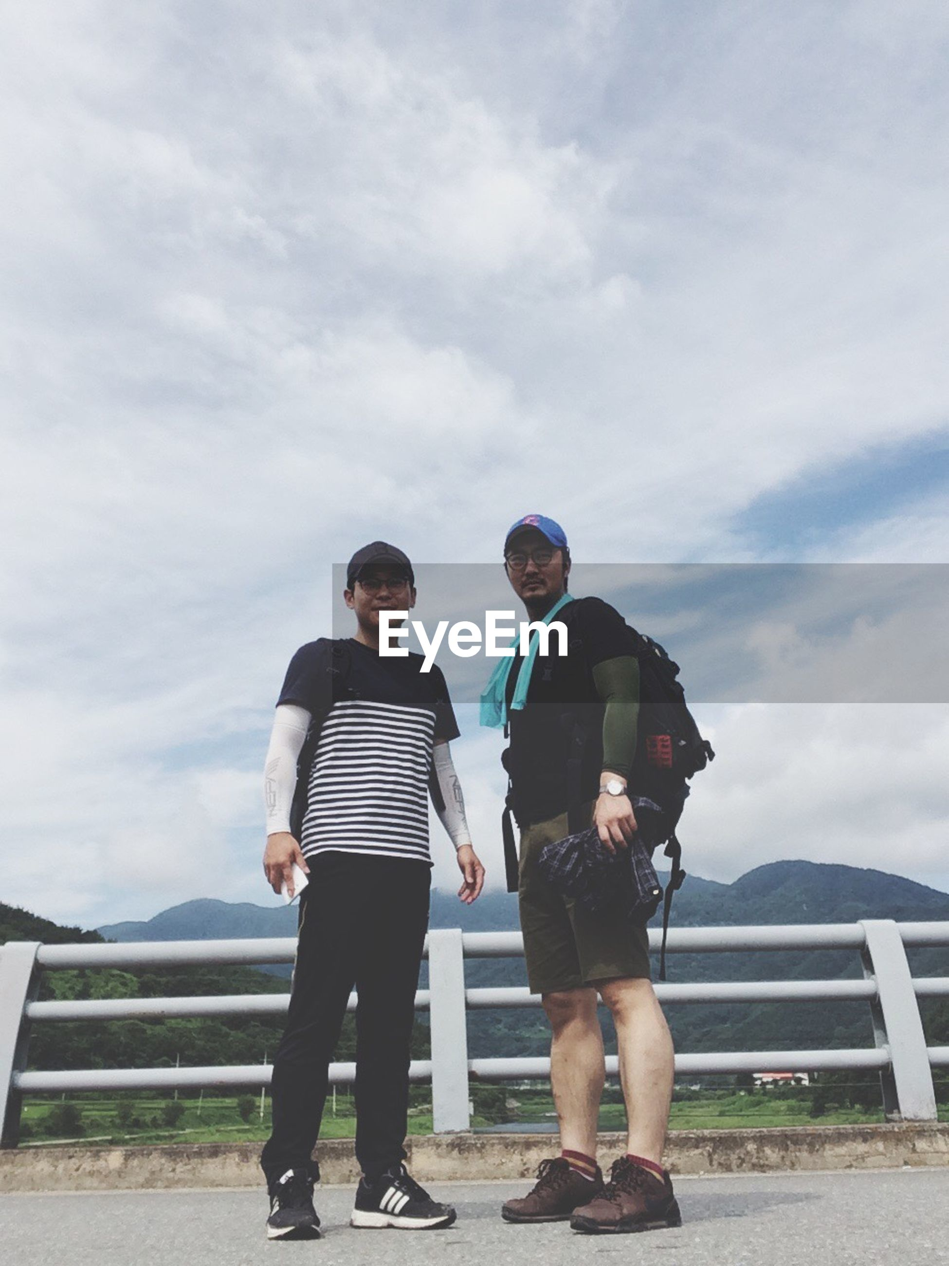 two people, real people, full length, casual clothing, sky, lifestyles, young men, leisure activity, mature men, young adult, standing, day, outdoors, cloud - sky, togetherness, men, mountain, nature, young women, people
