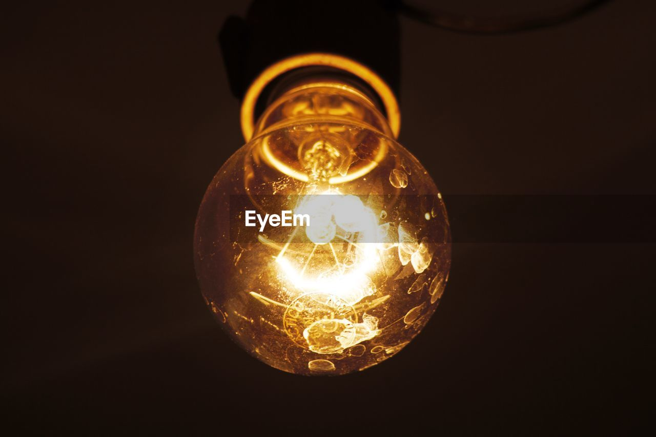 electricity, illuminated, lighting equipment, light bulb, close-up, glowing, no people, black background, low angle view, yellow, filament, hanging, indoors, technology