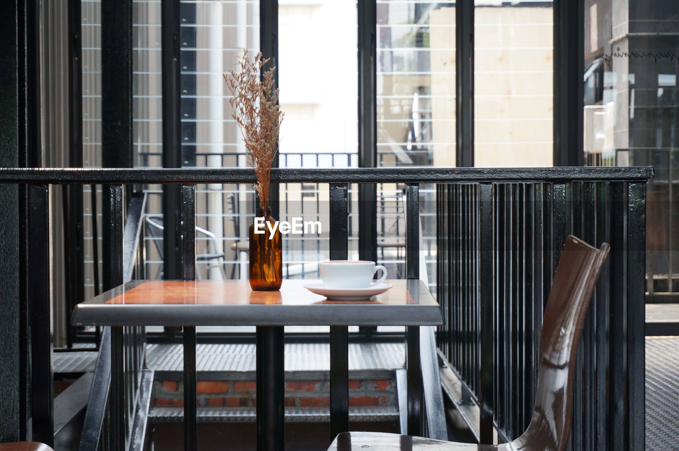 Empty chair with table by railing in cafe
