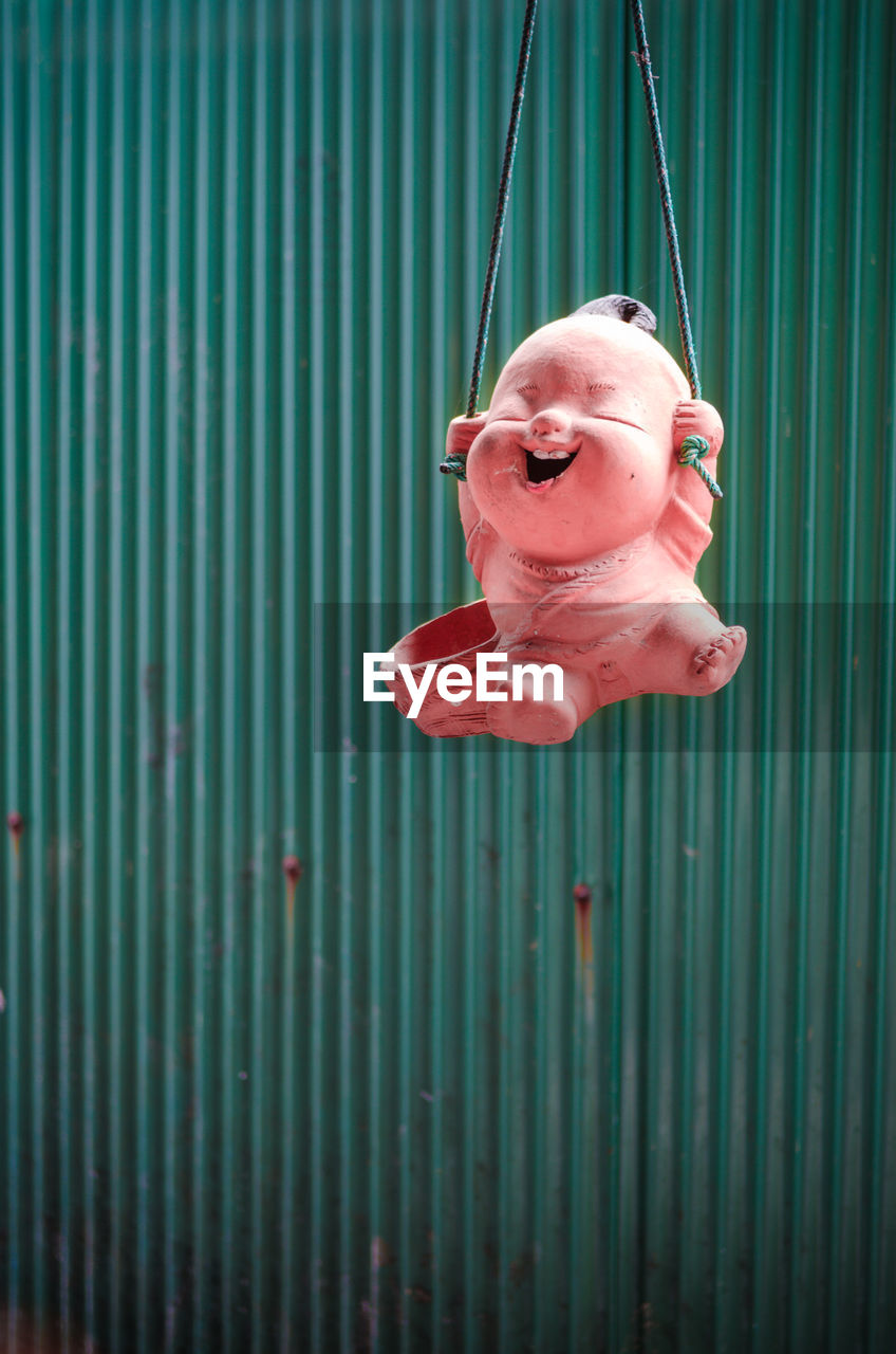 Toy Hanging Against Corrugated Iron