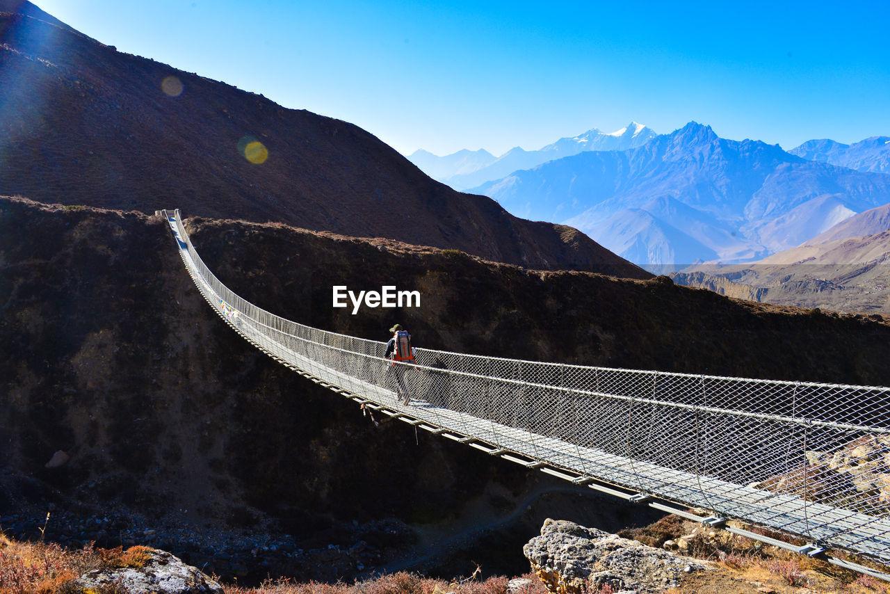 Person Walking On Bridge Against Mountains