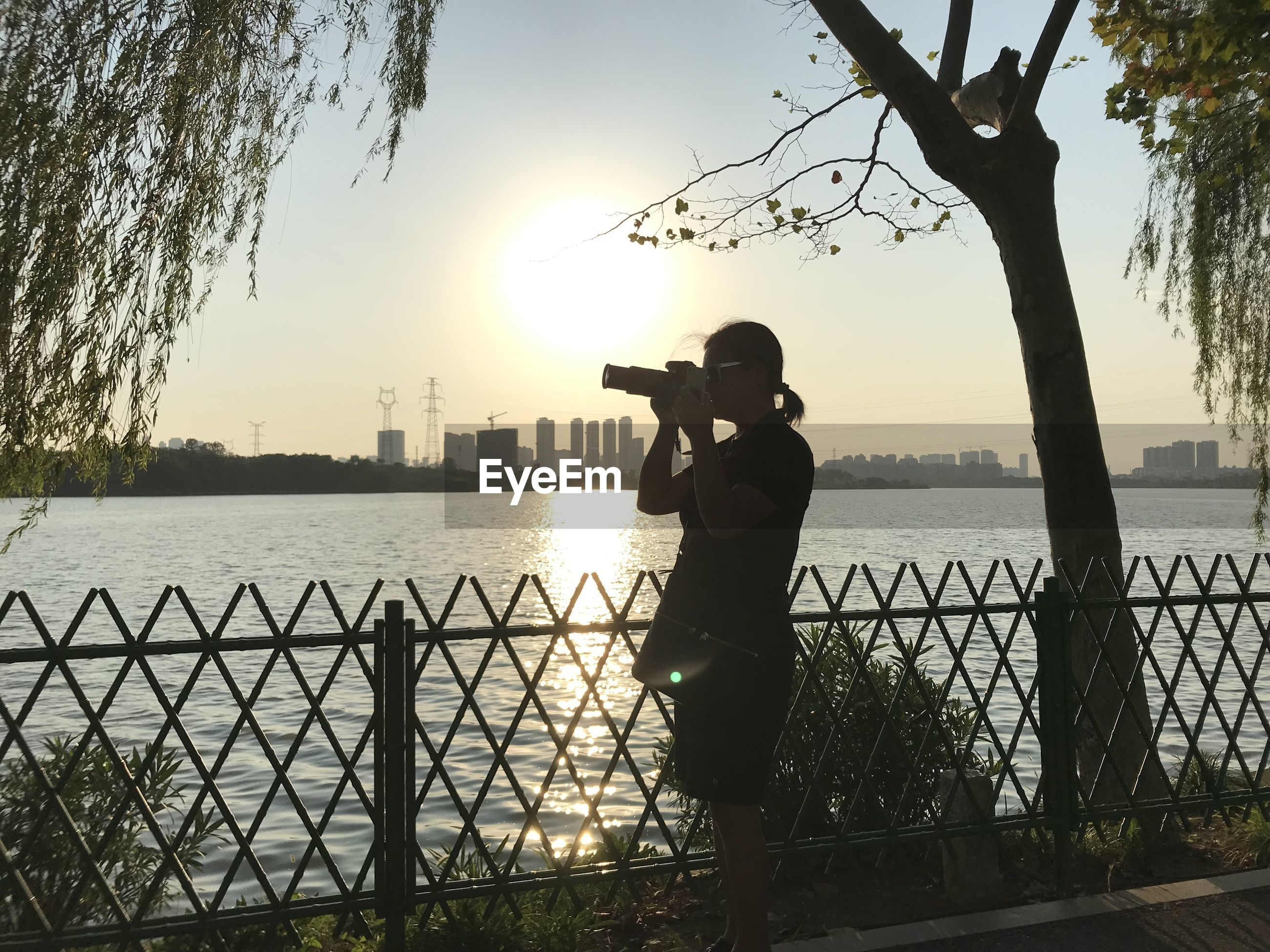 Woman photographing by railing against river during sunset