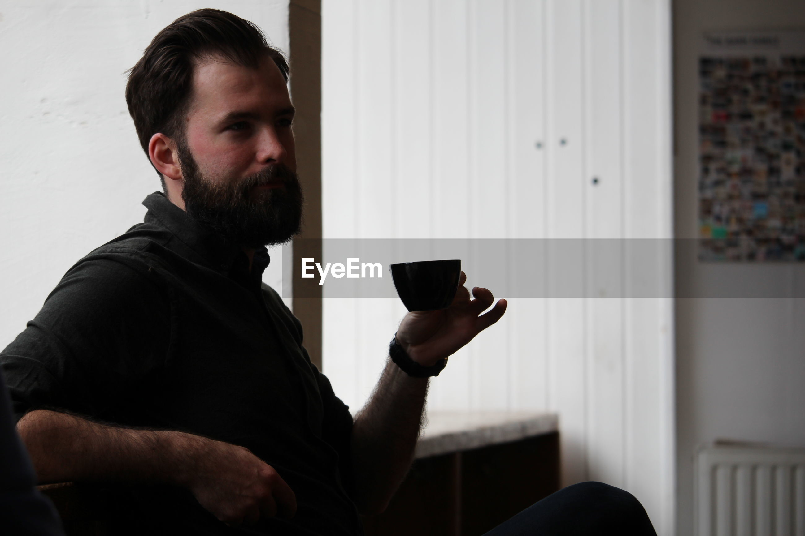 Young man holding coffee cup while sitting on sofa at home