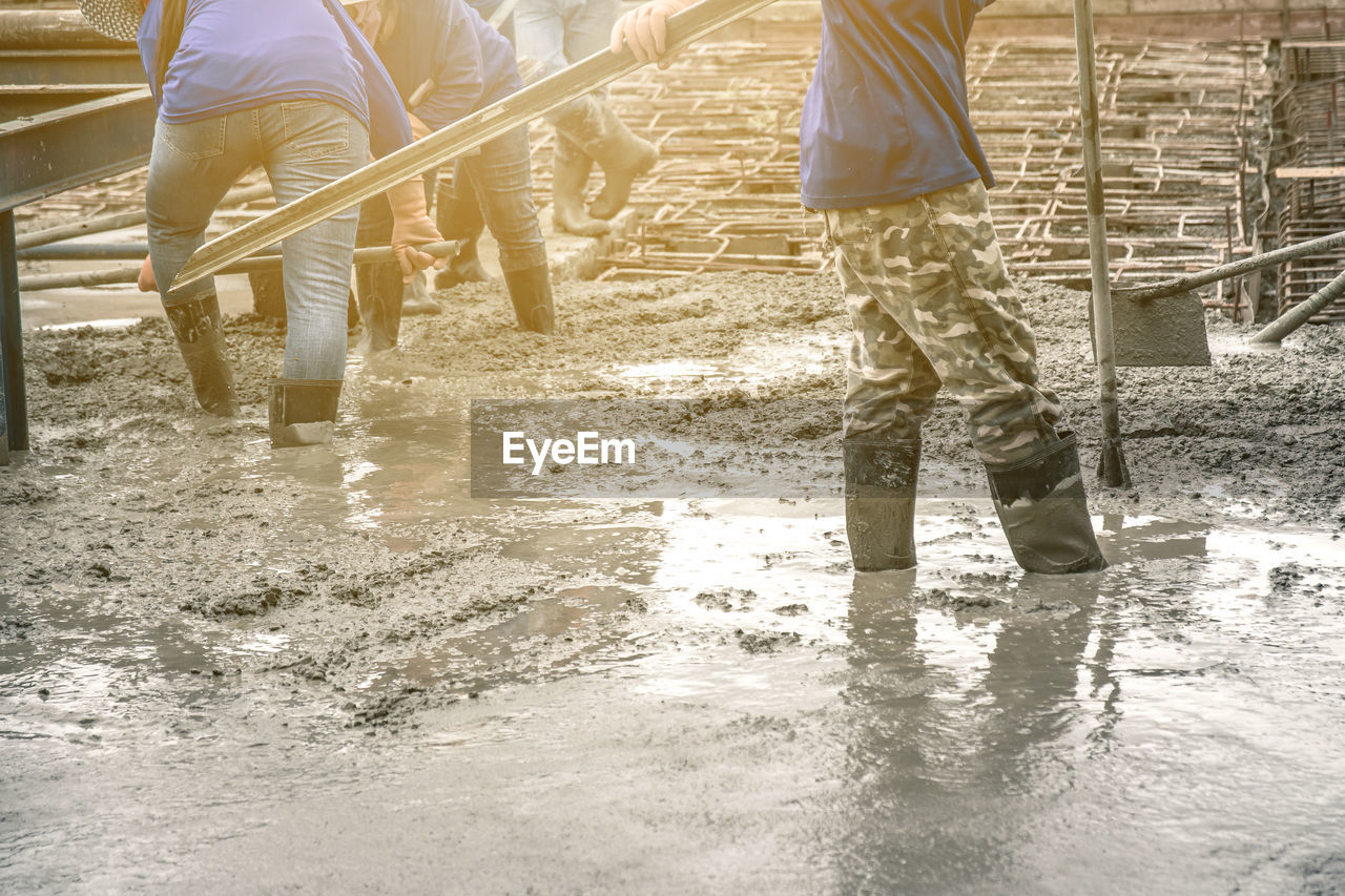 water, low section, body part, shoe, human leg, group of people, human body part, boot, puddle, nature, architecture, walking, wet, day, motion, rubber boot, people, reflection, standing, outdoors, human limb, rain