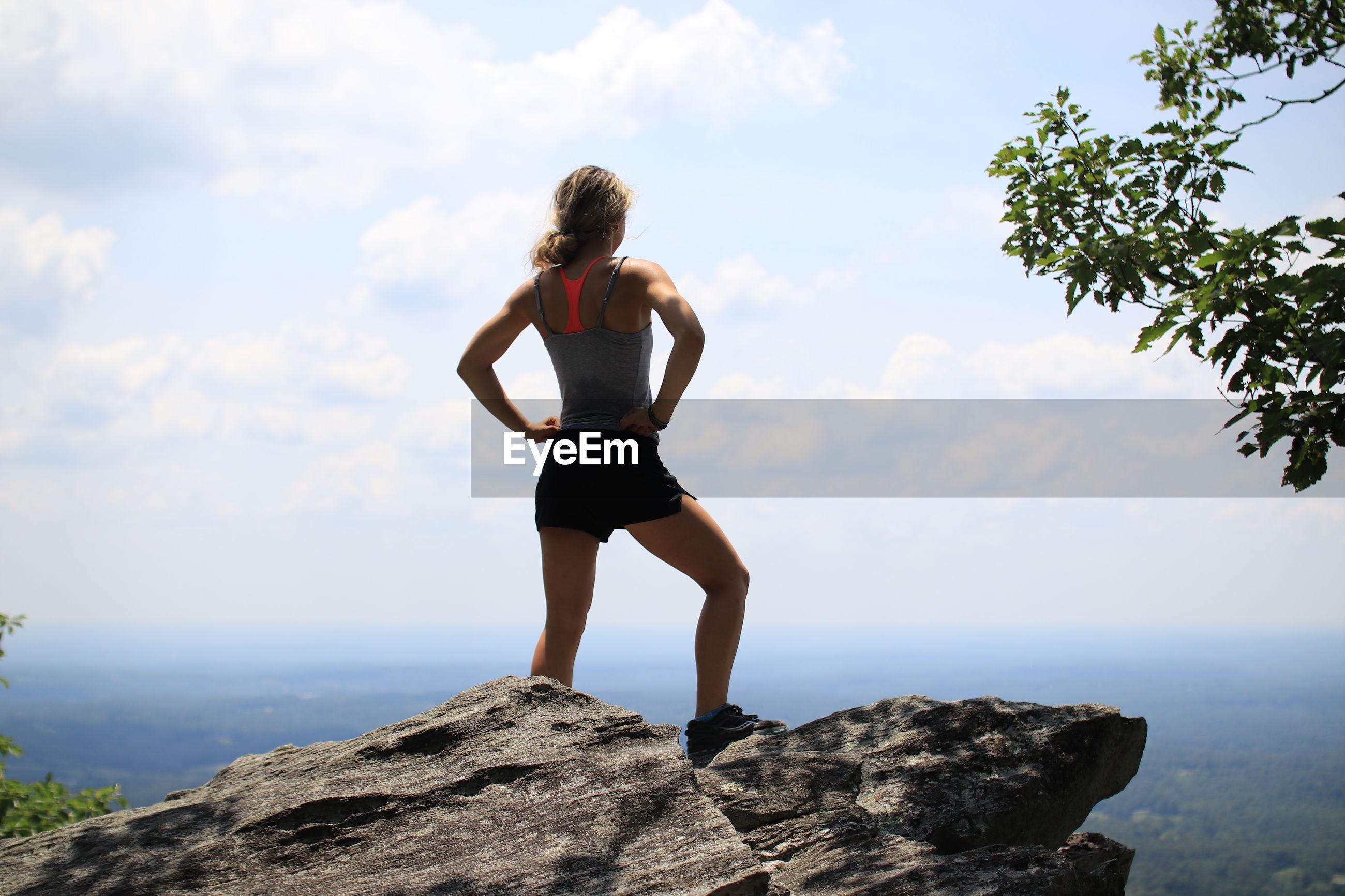 Full length of woman standing on mountain rock by clouds against sky
